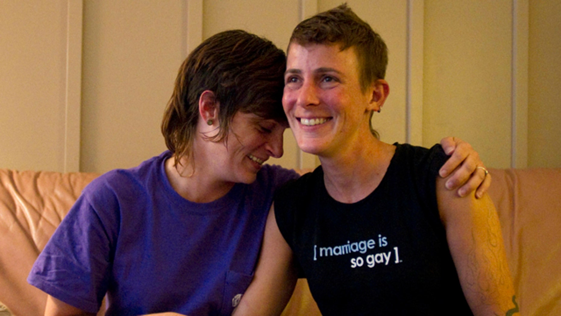 July 25: Lesbian couple Jennifer Tipton, left, and Olivier Odom are seen at a coffee house in Knoxville, Tenn. The couple are calling for Dollywood Splash County to be more inclusive to its guests after they were asked to reverse the pro-gay marriage T-shirt worn by Odom, during a recent visit.