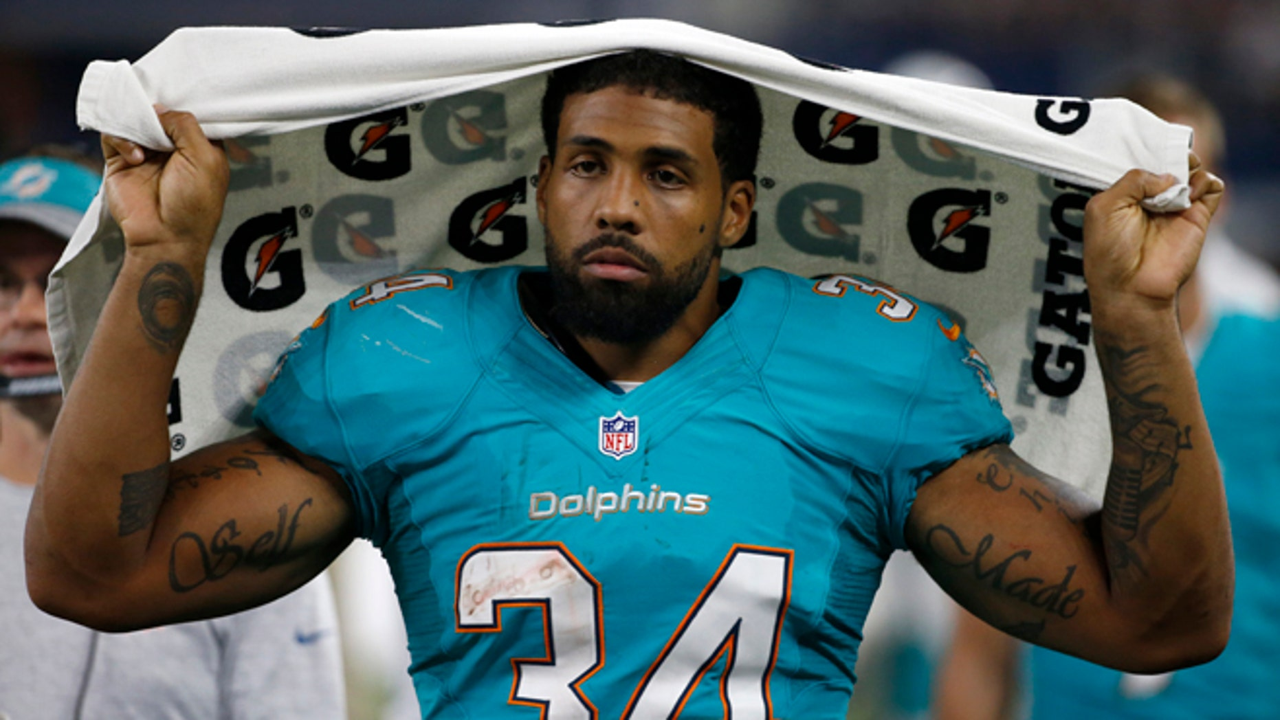 This Aug. 19, 2016 photo shows Miami Dolphins running back Arian Foster (34) walking along the sideline during an NFL preseason football game in Arlington, Texas. Four-time Pro Bowl running back Arian Foster has announced, Monday, Oct. 24, 2016, his retirement midway through an injury-plagued season with the Miami Dolphins. (AP Photo/Michael Ainsworth)