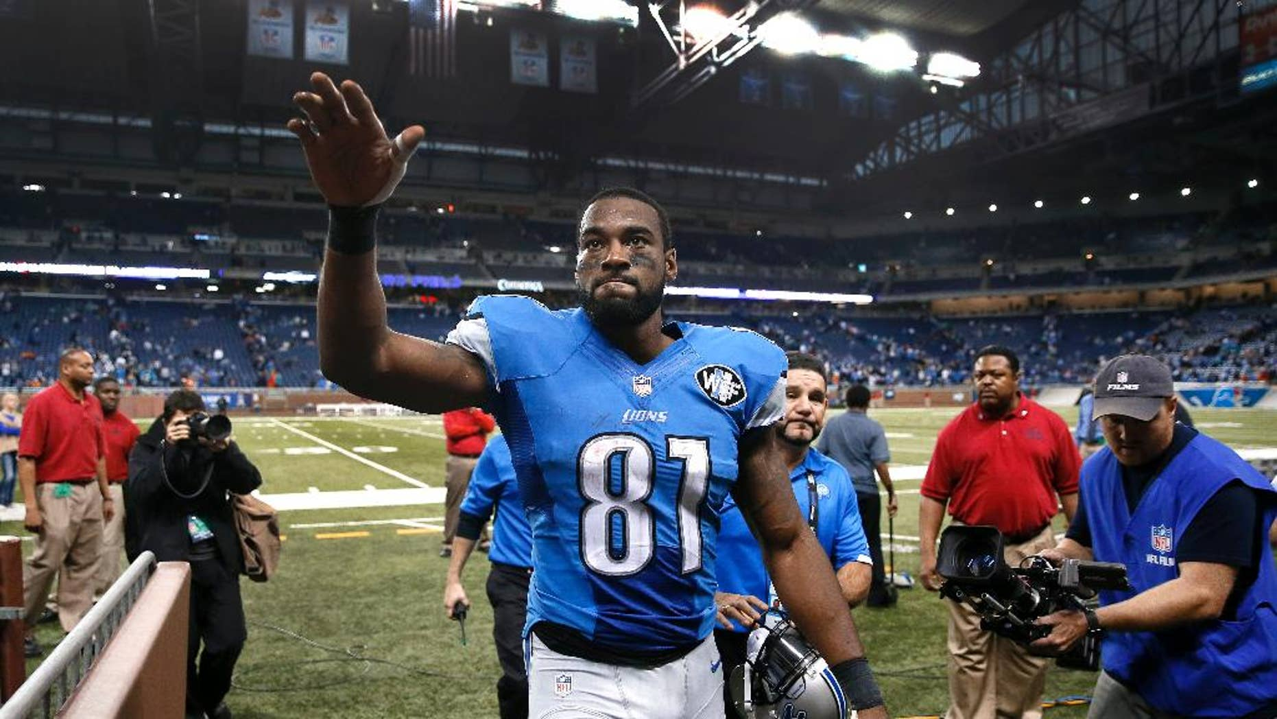 Detroit Lions wide receiver Calvin Johnson waves to fans after defeating the Miami Dolphins 20-16 in a NFL football game in Detroit, Sunday, Nov. 9, 2014. (AP Photo/Paul Sancya)