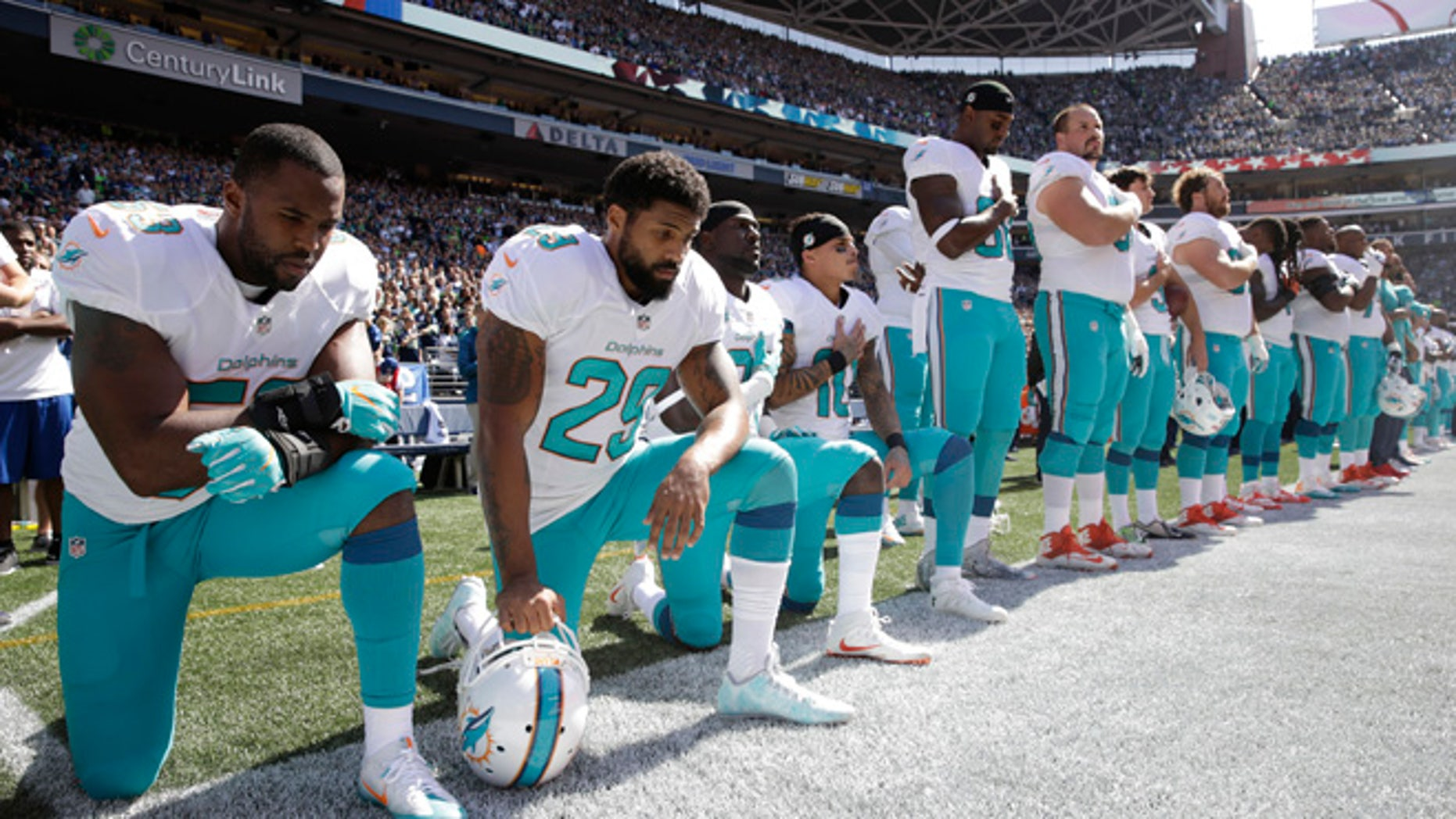 Jelani Jenkins, Arian Foster, Michael Thomas and Kenny Stills during the national anthem on Sept. 11, 2016, in Seattle.