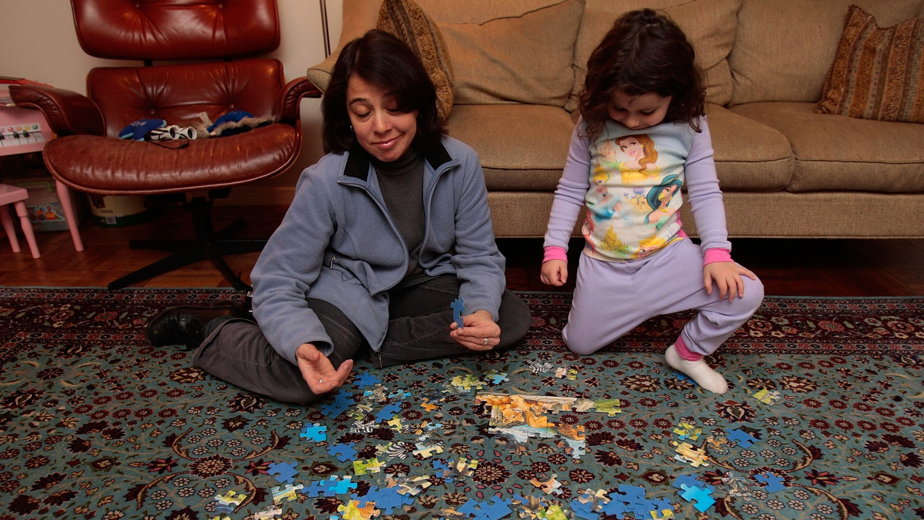 """NEW YORK - DECEMBER 11:  Jocelyn Taub, a job-hunting marketing professional, works on a puzzle with a three-year-old girl while babysitting for extra money December 11, 2008 in New York City.  Taub has worked in the music promotion and radio business her whole career, but was let go from her job 10 months ago and has been job searching ever since.  To make ends meet, she's been working odd jobs in offices for friends and is doing some babysitting. """"I've seen downturns before, but it's never been like this,"""" she says.  (Photo by Chris Hondros/Getty Images)"""