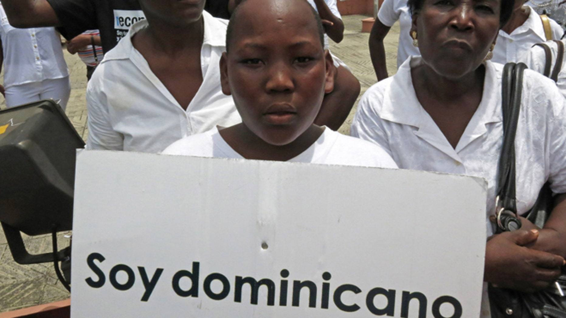 """FILE - In this Aug. 12, 2013 file photo, a youth of Haitian descent holds a sign that reads in Spanish """"I'm Dominican"""" during a protest demanding that President Danilo Medina stop the process to invalidate their birth certificates after authorities retained their ID cards, in Santo Domingo, Dominican Republic. The Dominican Republic's top court on Thursday, Sept. 26, 2013 stripped citizenship from thousands of people born to migrants who came illegally, a category that overwhelmingly includes Haitians brought in to work on farms. The decision cannot be appealed, and it affects all those born since 1929. (AP Photo/Ezequiel Abiu Lopez, File)"""