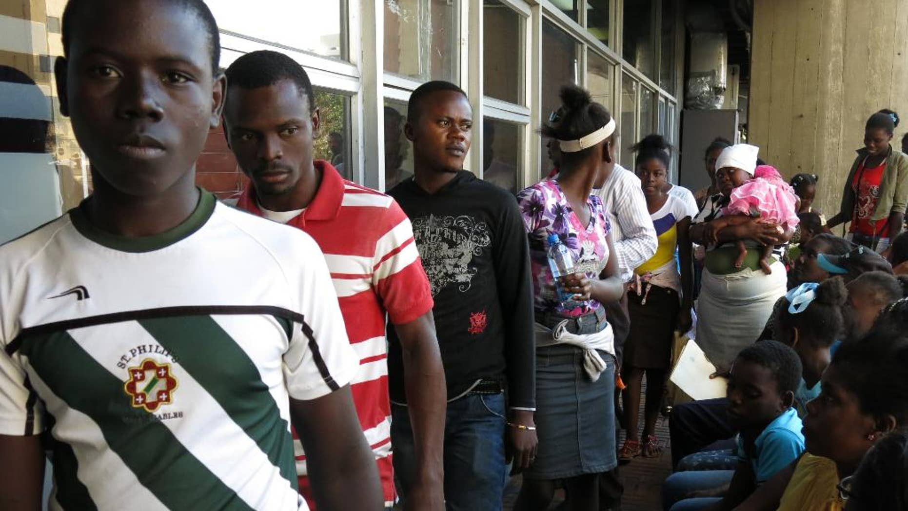 People of Haitian descent born in the Dominican Republic stand in line to apply for a birth certificate listing them as foreigners, in Santo Domingo, Dominican Republic, Thursday, Jan. 29, 2015. The government says people have until Feb. 1 to apply for birth certificates as foreigners, needed to gain legal status. (AP Photo/Ezequiel Abiu Lopez)