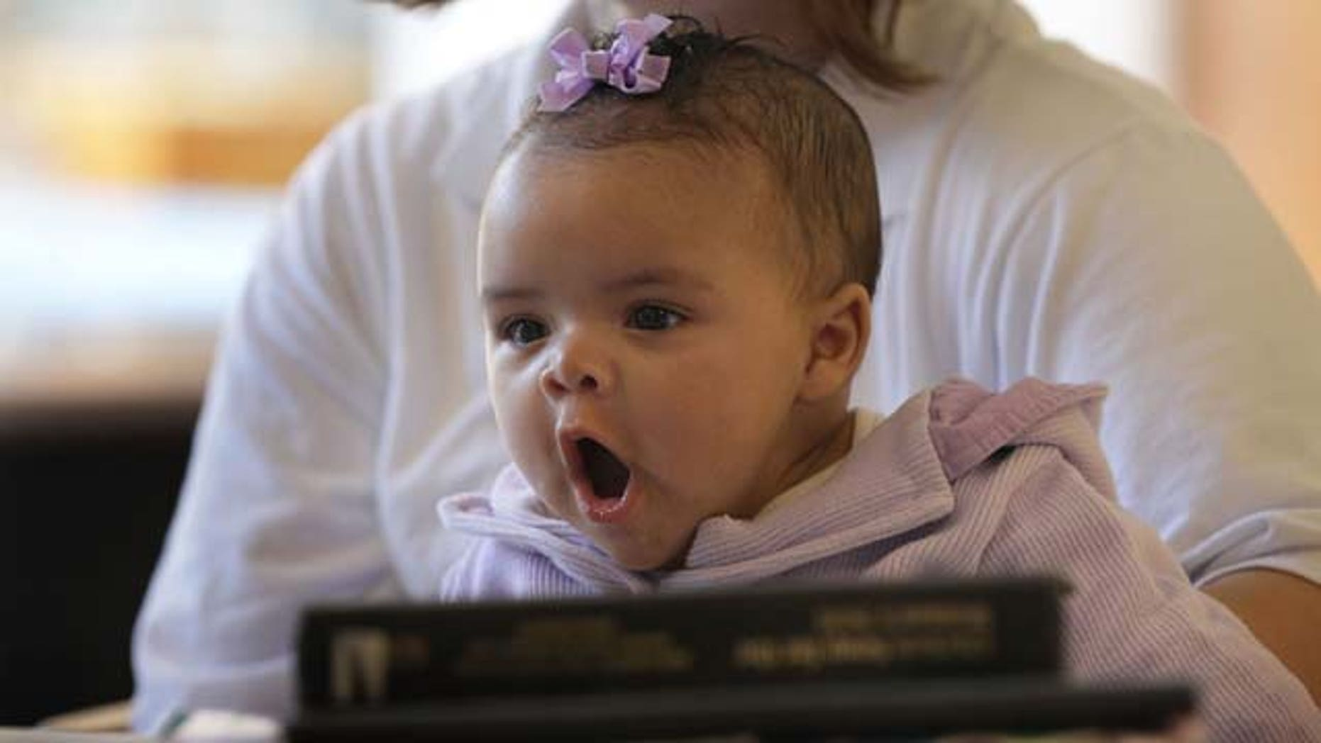 DECATUR, IL - FEBRUARY 18: Three-month-old  Alexis sits on her mother's lap in the common area of her ward at the Decatur Correctional Center February 18, 2011 in Decatur, Illinois. Alexis, who was born while her mother Brandi Ceci was serving a 54 month sentence for burglary, lives with her mother at the prison, part of the Moms with Babies program at the minimum security facility. The program allows incarcerated women to keep their newborn babies with them for up to two years while serving their sentence. The program boasts a zero percent recidivism rate compared to the statewide rate of 51.3 percent.  (Photo by Scott Olson/Getty Images)
