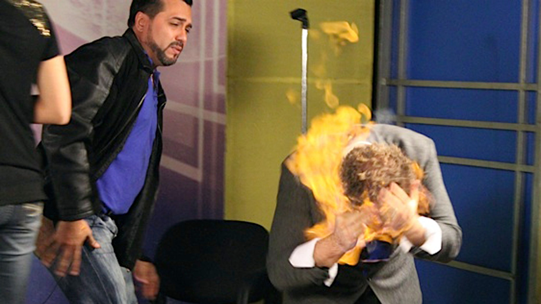 "Nov. 26, 2012: In this picture released by American magician Wayne Houchin, Dominican TV presenter Franklin Barazarte, left, watches as Houchin's head burns while taping ""Closer To The Stars"" TV program in Santo Domingo, Dominican Republic."