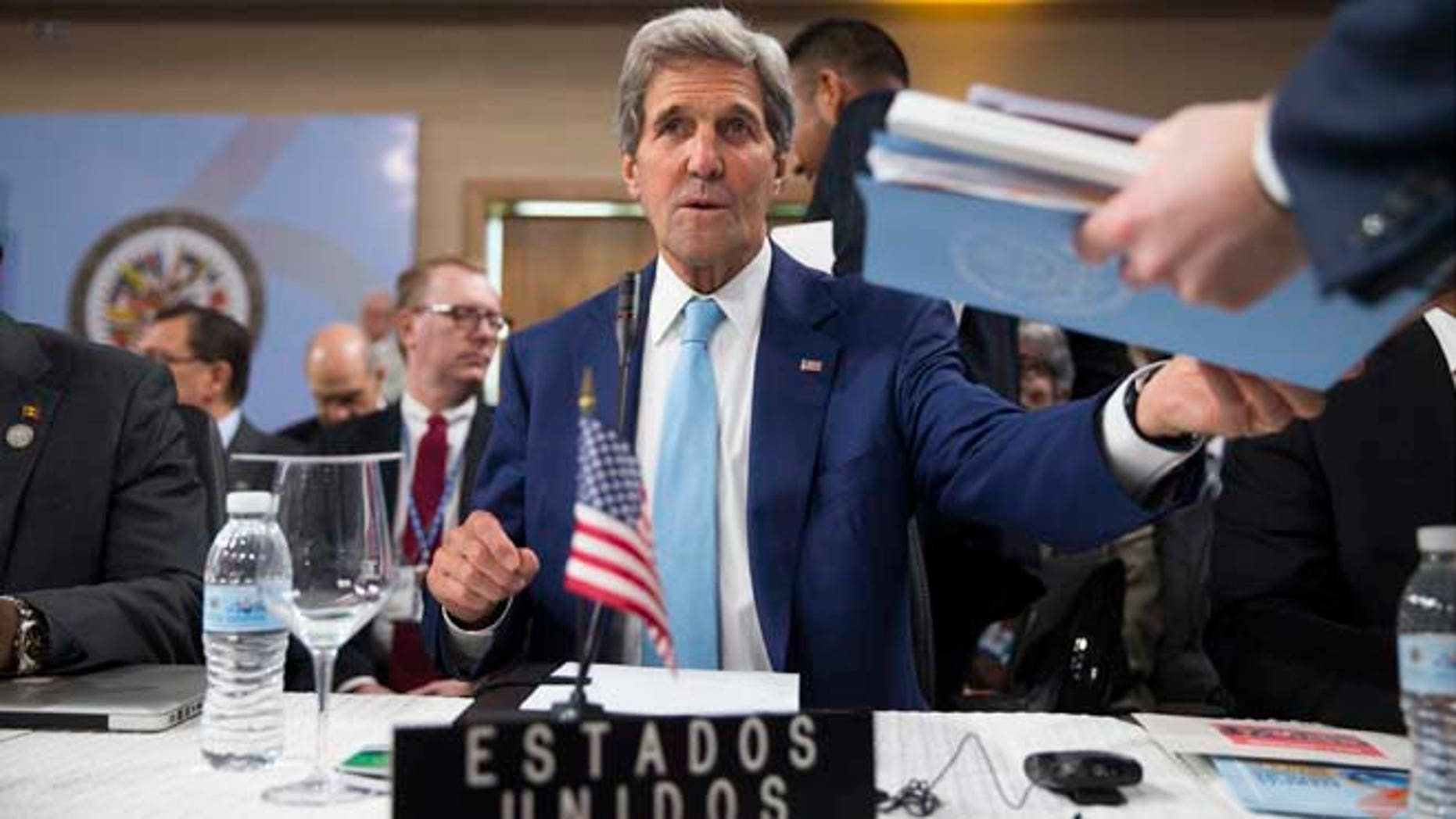 Secretary of State John Kerry is handed notes as he sits down for the General Assembly of the Organization of American States, Tuesday, June 14, 2016, in Santo Domingo, Dominican Republic. (AP Photo/Evan Vucci, Pool)