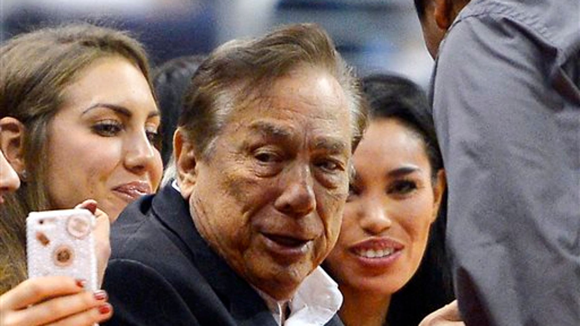 Donald Sterling and V. Stiviano, right, watch the Clippers play the Sacramento Kings on Friday, Oct. 25, 2013.