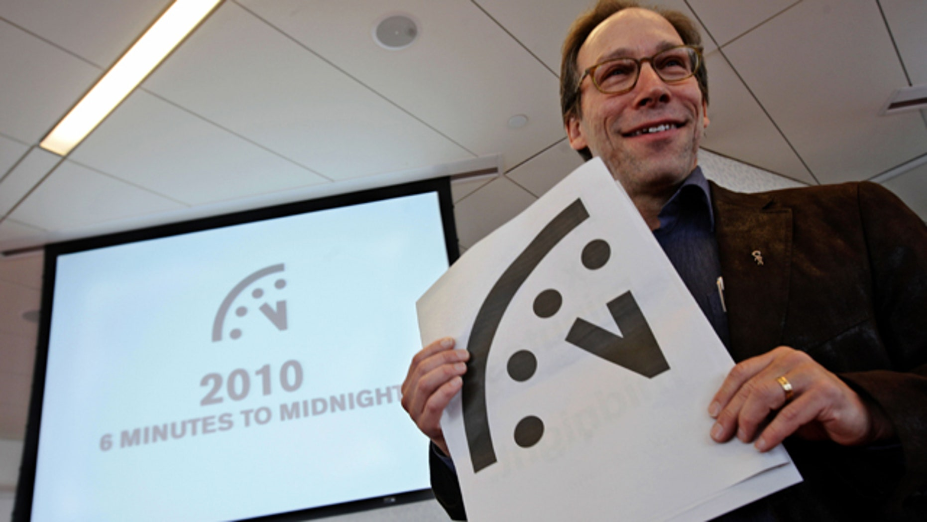 """Lawrence Krauss, co-chair of the Bulletin of Atomic Scientists Board of Sponsors poses with a graphic image of the """"Doomsday Clock"""" during a news conference."""
