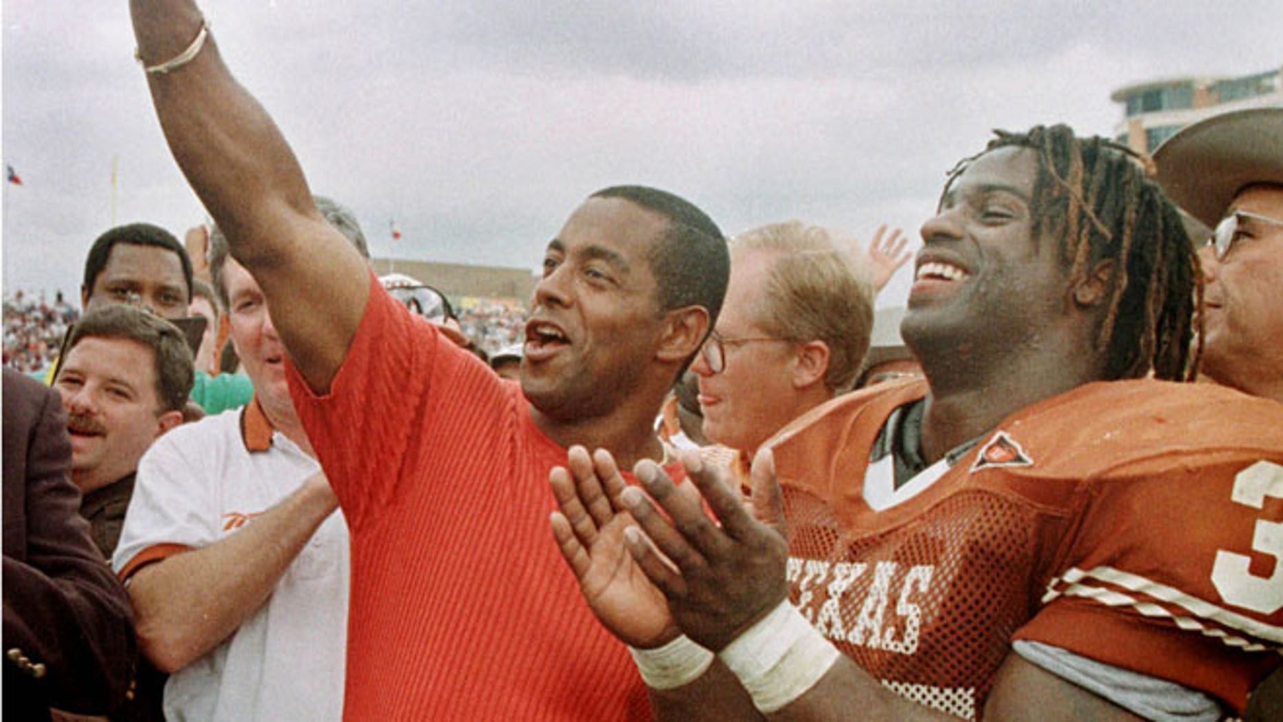 FILE: University of Texas Longhorns Ricky Williams, right, laughs as former Dallas Cowboys star Tony Dorsett signals 'Hook 'em horn' after Williams surpassed Dorsett's NCAA rushing record.