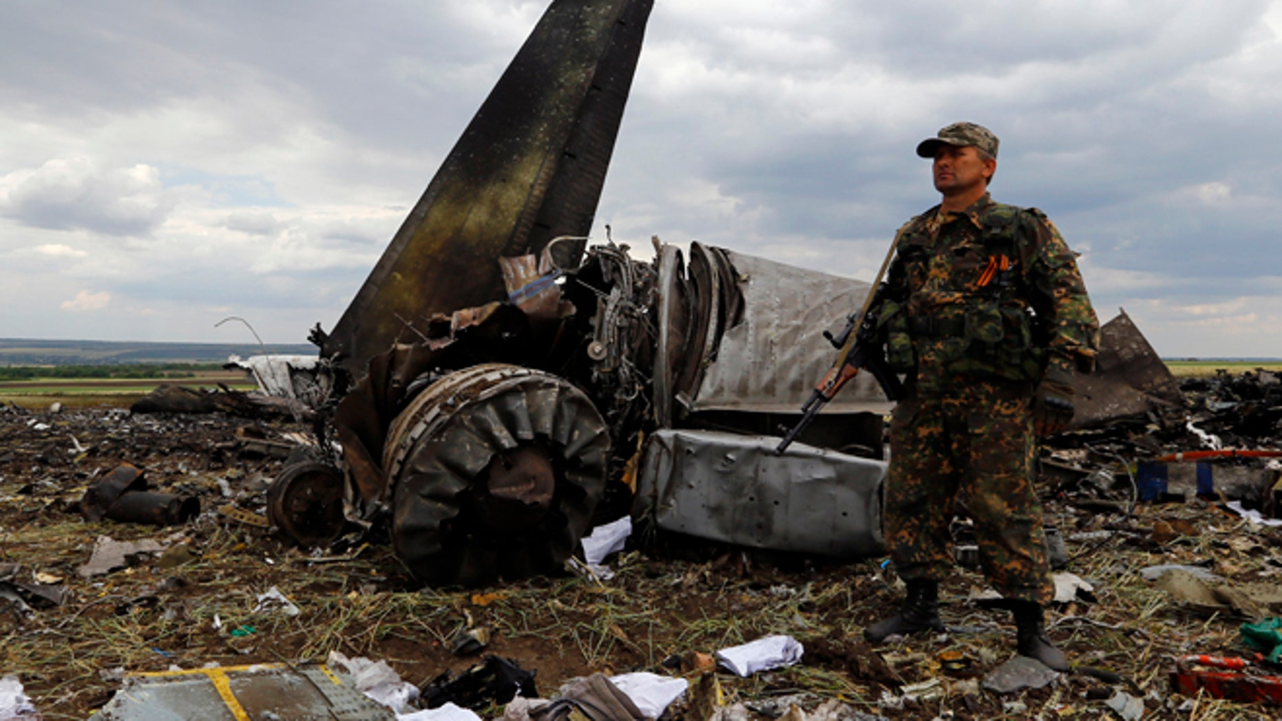 June 14: An armed pro-Russian separatist stands guard at the site of the crash of the Il-76 Ukrainian army transport plane in Luhansk.