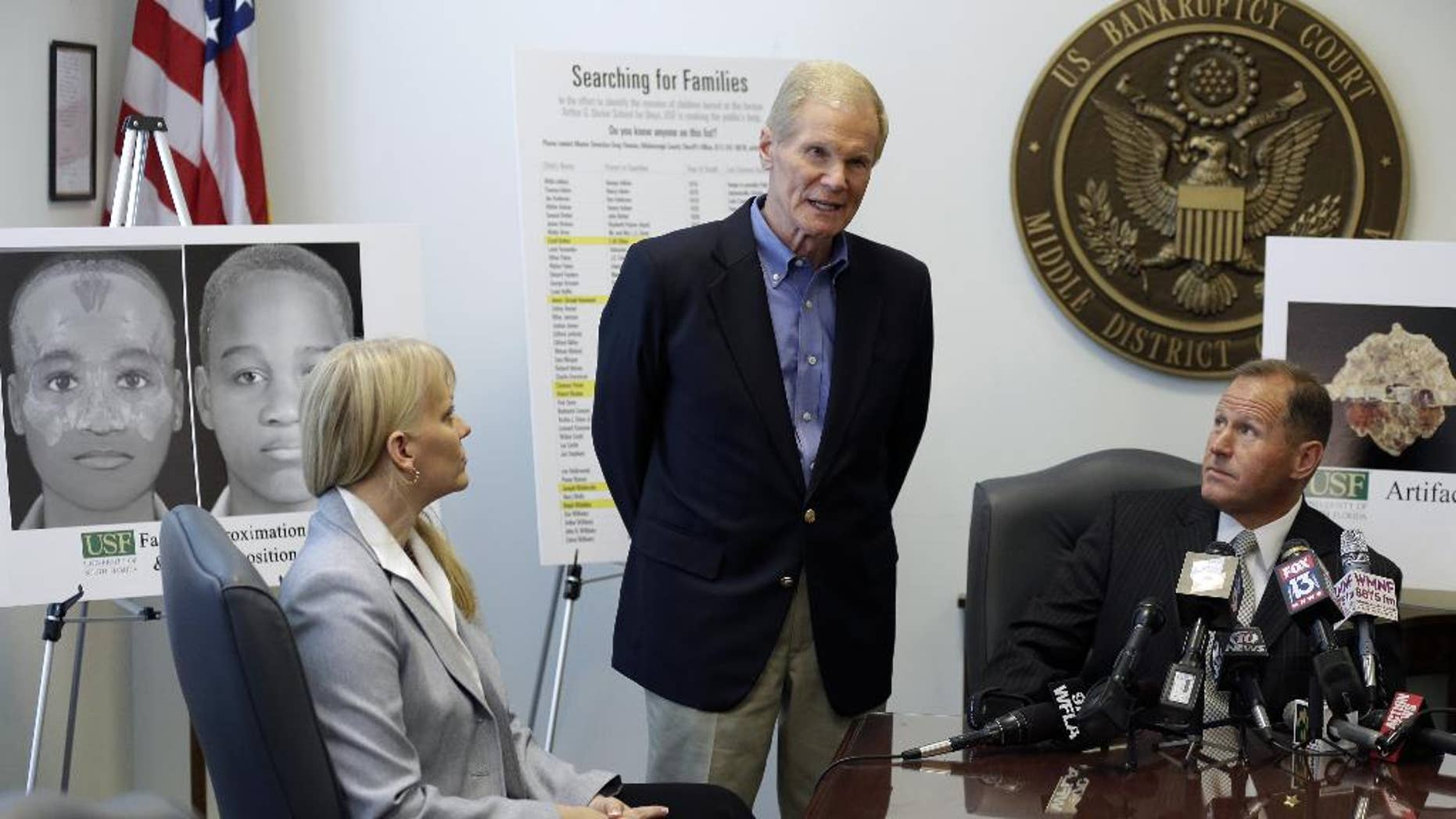 FILE - In this April 15, 2014, file photo, U.S. Sen. Bill Nelson, center, D-Fla., along with University of South Florida Associate Professor Erin Kimmerle, left, and Hillsborough County Sheriff David Gee, right, speak to the media about the on-going research being done at the Arthur G. Dozier School for Boys in Marianna, Fla., at the United States Courthouse, in Tampa, Fla. Researchers studying dozens of graves and deaths at a now closed Florida reform school describe a long history of horrific treatment of the boys. A report released by University of South Florida researchers this week identifies two more of the people buried in the graves. (AP Photo/Chris O'Meara, File)