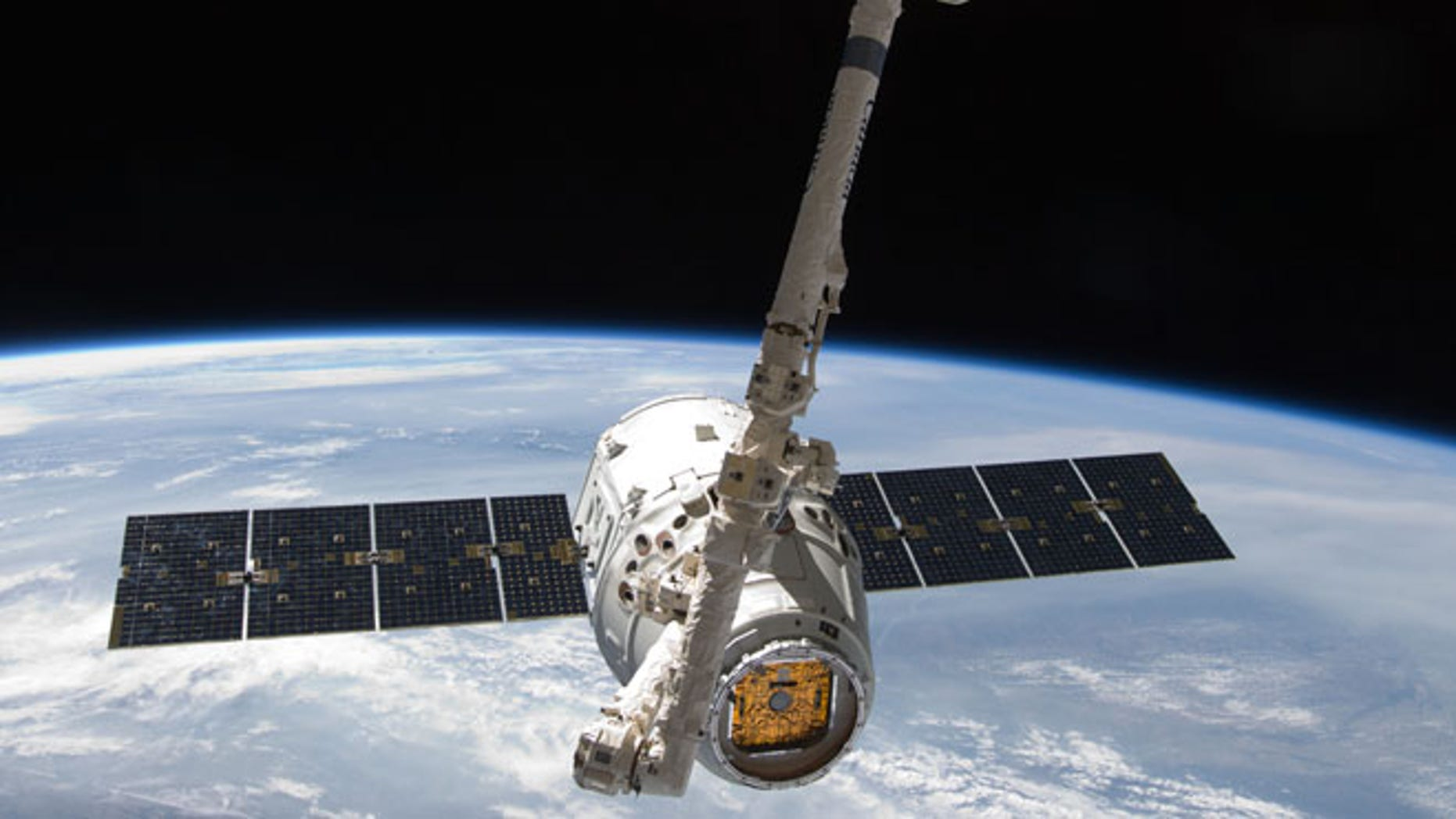 May 25, 2012: View from the International Space Station of the SpaceX Dragon spacecraft as the stations robotic arm moves Dragon into place for attachment to the station.