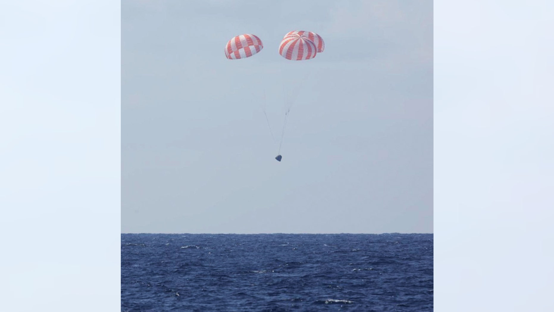 In this photo made available by SpaceX, the Dragon capsule uses parachutes to land in the Pacific Ocean near Southern California, returning from the International Space Station in orbit on Thursday, May 21, 2015.