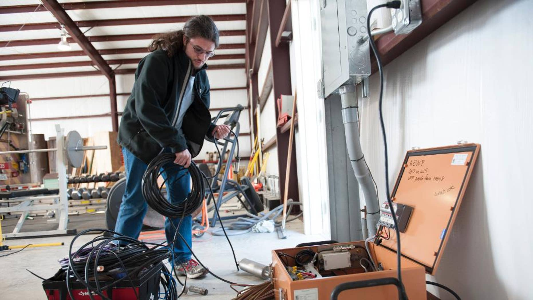 """This handout photo, taken Jan. 16, 2014, provided by Southern Methodist University, shows Remi Oldham, an SMU geophysics graduate student, running a cable to connect the seismometer to communications interface equipment housed in the orange metal box in Willow Park, Texas. The interface equipment allows the transmission of the data collected by the seismometer back to SMU. With real-time monitors, scientists linked a swarm of small earthquakes west of Fort Worth, Texas, to nearby natural gas wells and wastewater injection. In 84 days from November 2013 to January 2014, the area around Azle, Texas, shook with 27 magnitude 2 or greater earthquakes, while scientists at Southern Methodist University and the U.S. Geological Survey monitored the shaking. It's an area that had no recorded quakes for 150 years on faults that """"have been inactive for hundreds of millions of years,"""" said SMU geophysicist Matthew Hornbach. (Hillsman Stuart Jackson/SMU via AP)  SMU, Dedman School of Humanities, Geology, Research, Seismic, Off Campus, Willow Park, Texas, Secondary Fire Station, Heather Deshon, Chris Hayward, Remi Oldham"""
