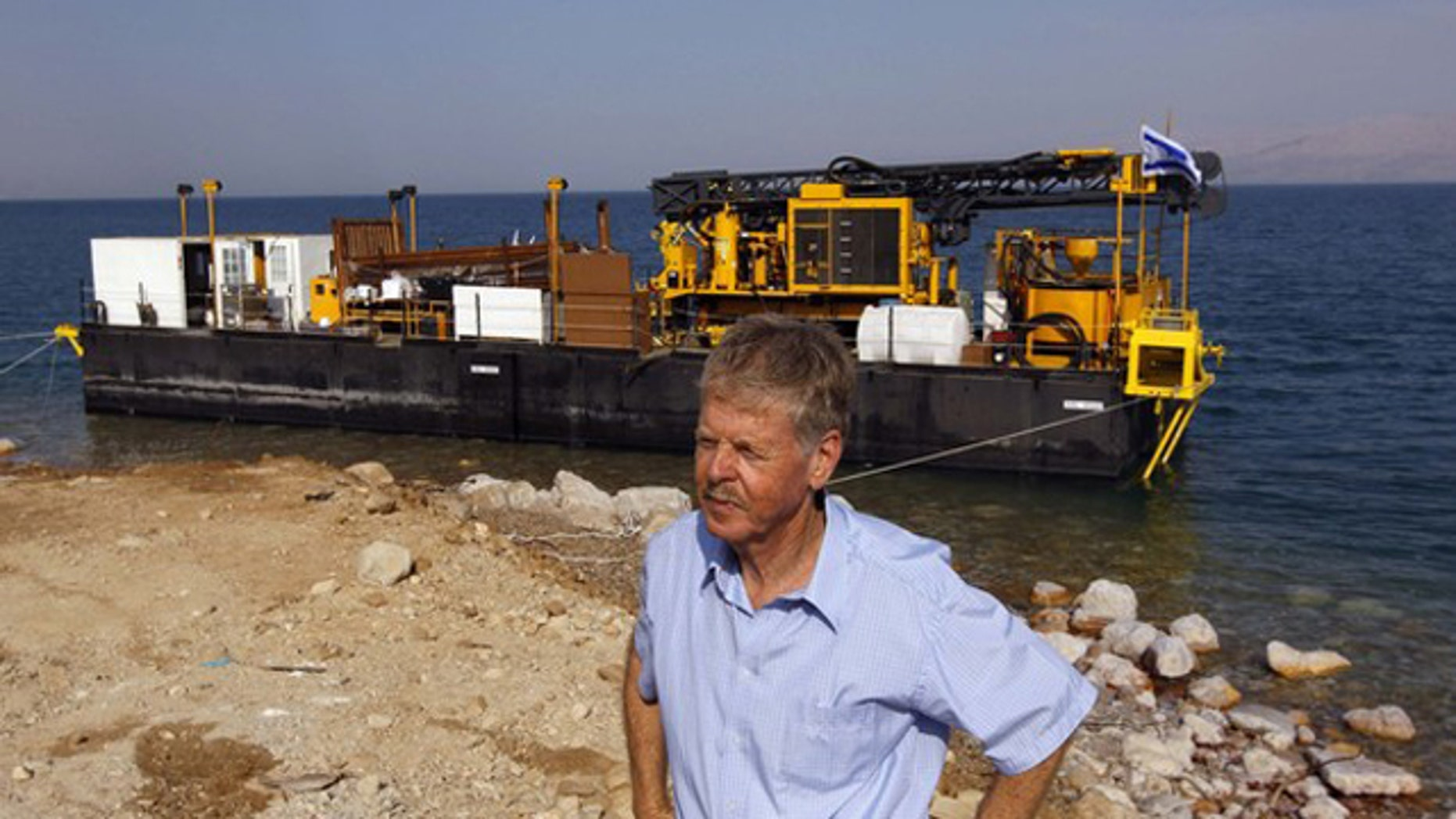 Zvi Ben-Avraham, head of the drilling project, stands in front of a moored drilling platform on the shore of the Dead Sea, near Kibbutz Ein Gedi November 16, 2010. A group of engineers and scientists will analyze 500,000 years of geological history, deciphering patterns and using them to find the best way to manage the earth's resources and environment.