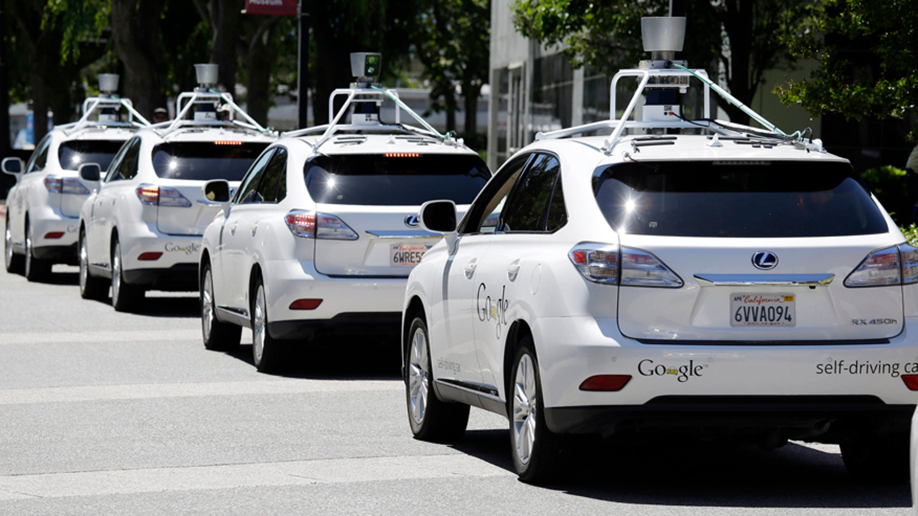 FILE - This May 13, 2014 file photo shows a row of Google self-driving cars in Mountain View, Calif. (AP Photo/Eric Risberg, File)