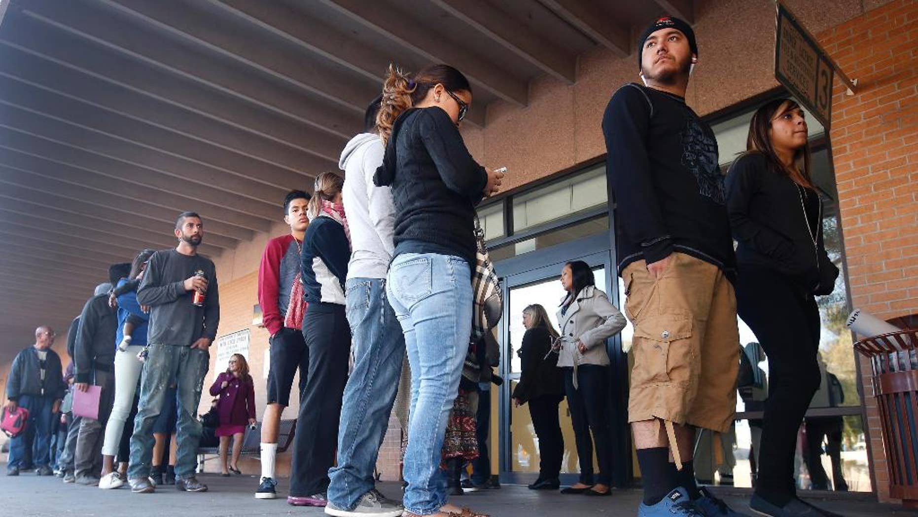 FILE - This Dec. 22, 2014 file photo a line stretches outside an a Arizona Department of Transportation Motor Vehicle Division office, begin pursuing Arizona driver's licenses. Only a small number of young immigrants who qualify for Arizona driver's licenses after a judge overturned a state ban have actually obtained licenses. Immigrant advocates say not enough people know they qualify. (AP Photo/Ross D. Franklin,File)