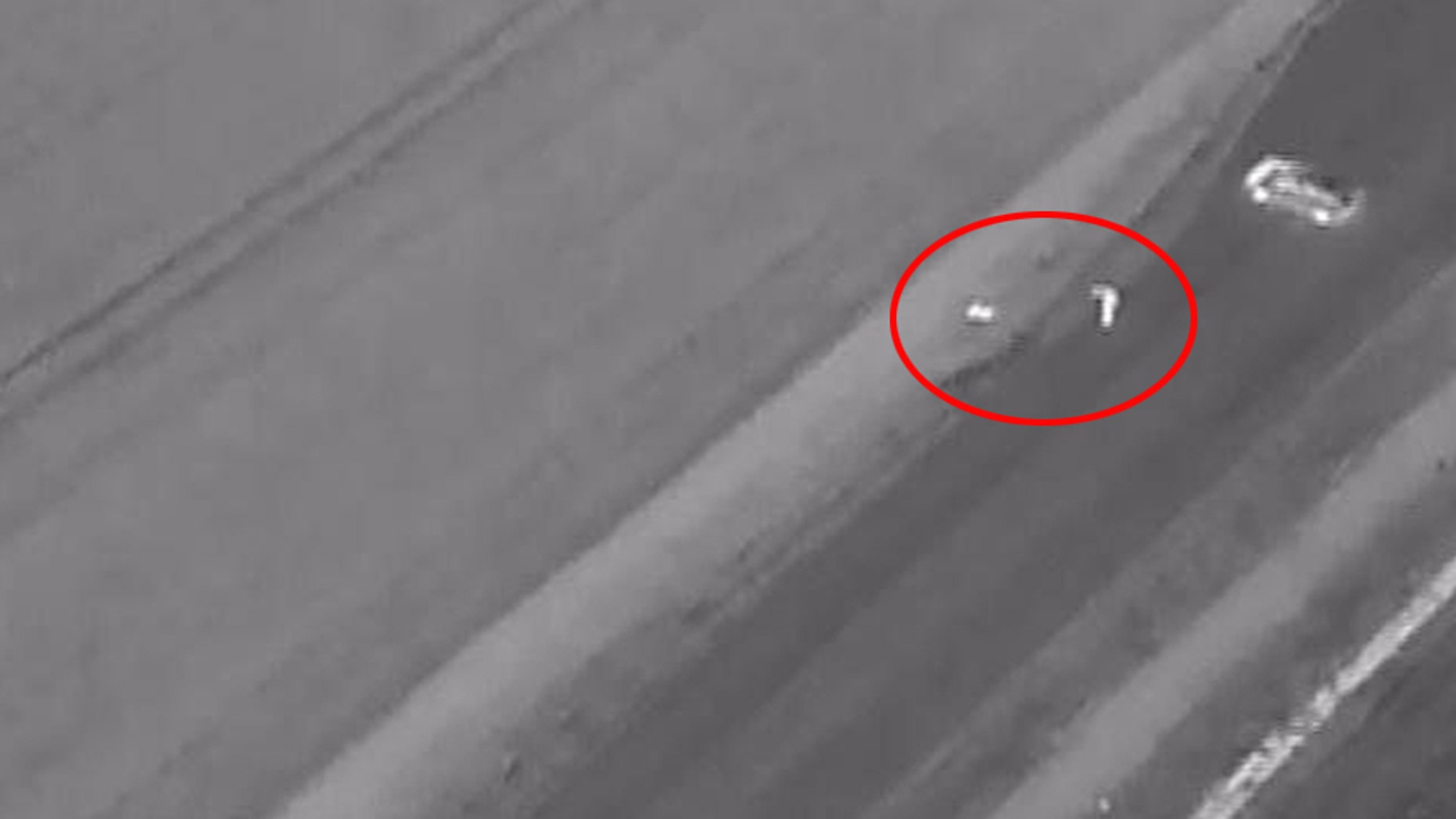 Drone footage shows a police officer (circled, right), finding the unconscious man (Lincolnshire Police)