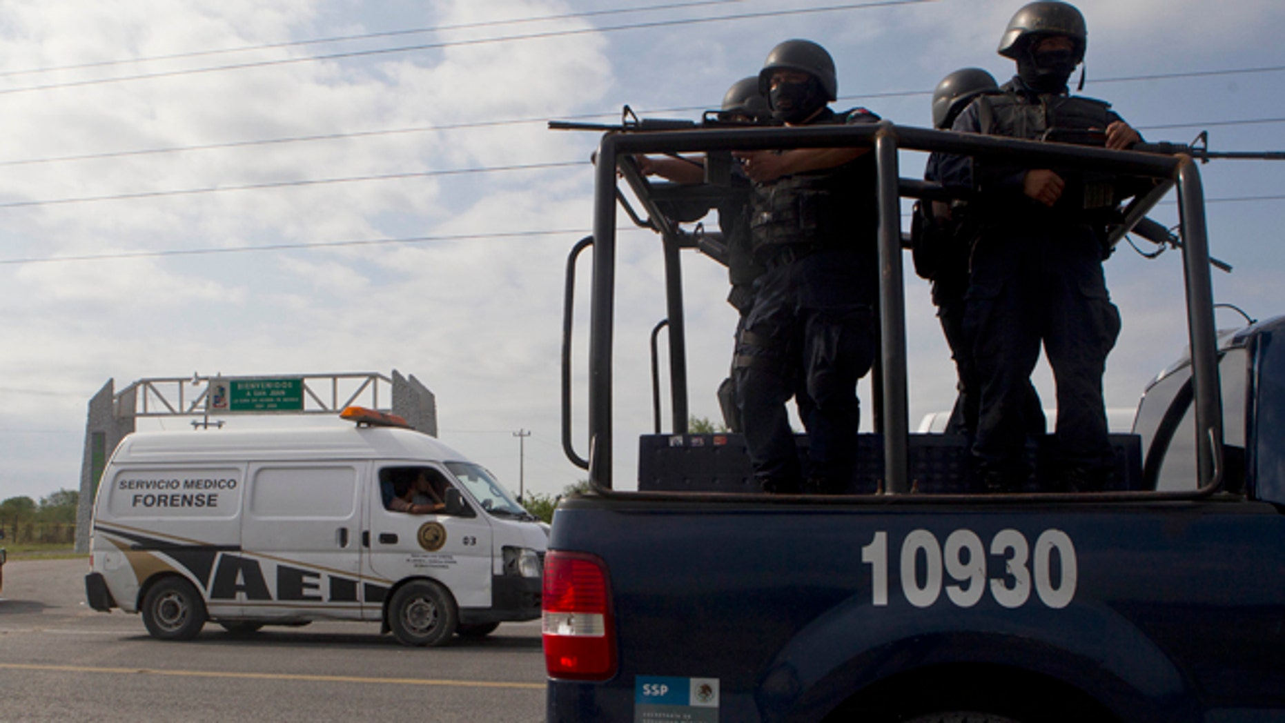 Federal police on a vehicle guard one of the three forensic trucks where several bodies were placed after dozens of bodies, some of them mutilated, were found on a highway connecting the northern Mexican metropolis of Monterrey to the U.S. border found in the Km 47 of the Reynosa-Cadereyta road in the town of San Juan near the city of Monterrey, Mexico,  Sunday, May 13, 2012. (AP Photo/Christian Palma)