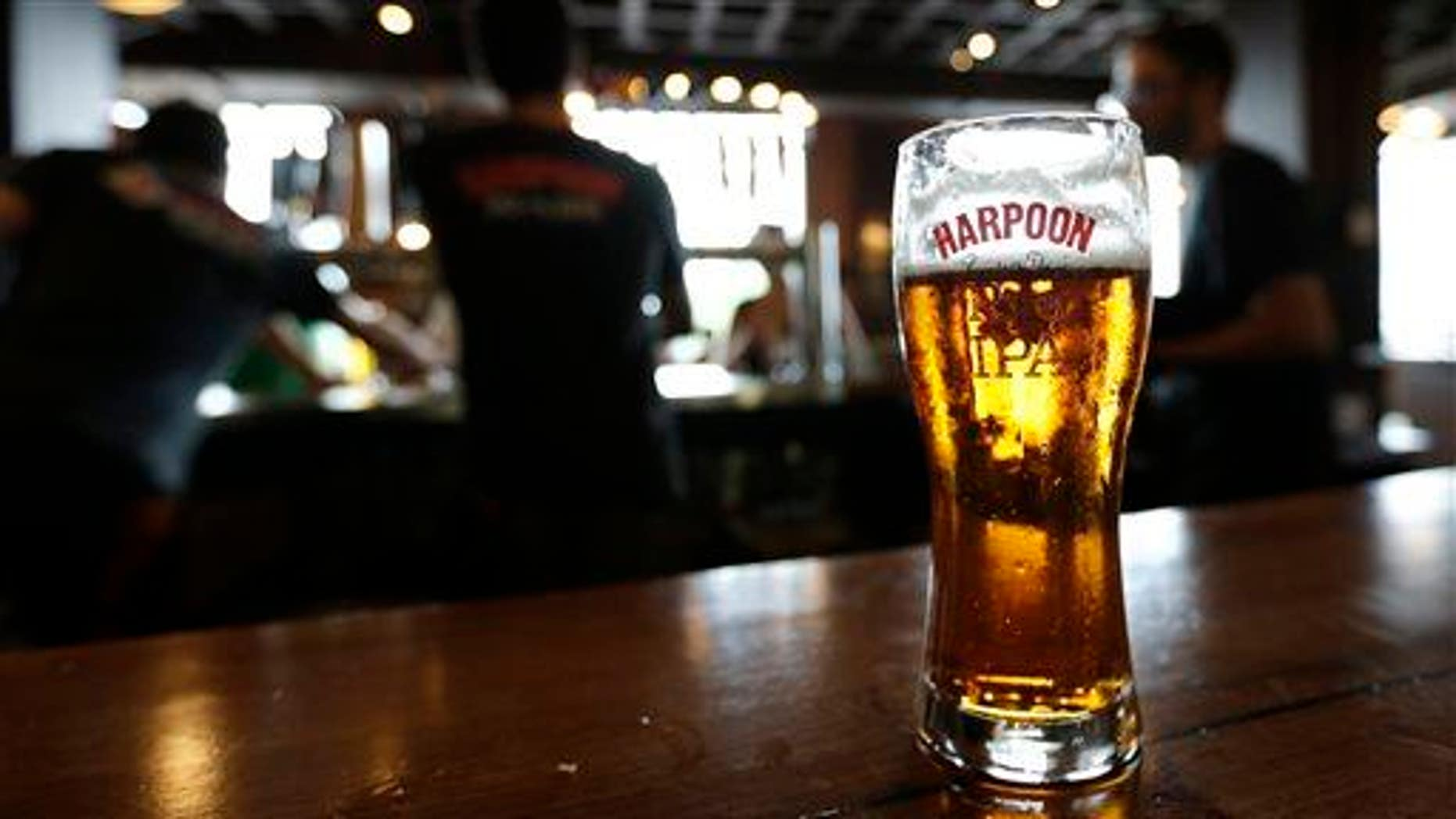 In this July 1, 2013 photo a glass of Rich and Dan's Rye IPA rests on the counter as bartenders pour drafts for patrons in the Beer Hall at the Harpoon Brewery in the Seaport District of Boston.