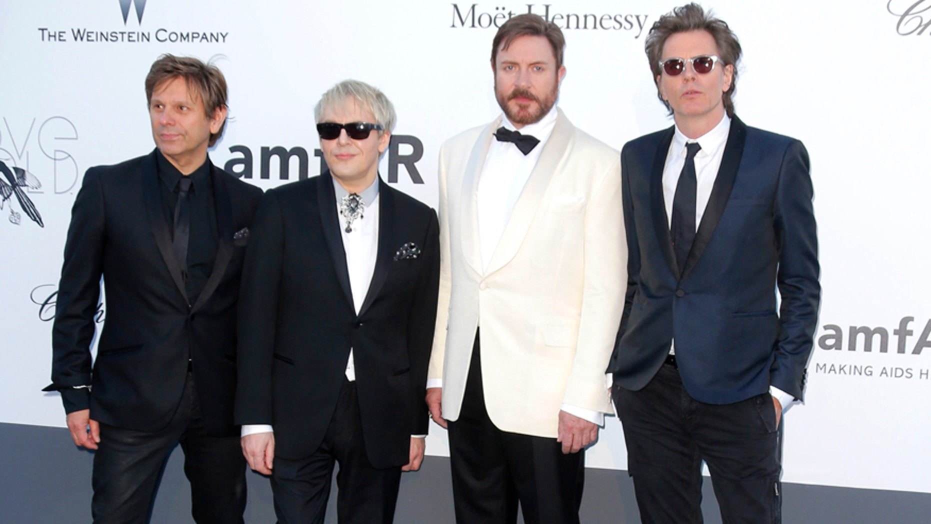"""FILE - This May 23, 2013 file photo shows members of Duran Duran, from left, Roger Taylor, Nick Rhodes, Simon Le Bon and John Taylor arrive at amfAR Cinema Against AIDS benefit during the 66th international film festival, in Cap d'Antibes, southern France. The group known for hits like """"Notorious"""" and """"Hungry Like the Wolf"""" accuses the suburban Chicago-based club of breaching contract by not forwarding promised revenue to the band. The Chicago Sun-Times reports that Duran Duran's lawsuit names Glenview-based Worldwide Fan Clubs, Inc. as the defendant. The suit was filed in Cook County Circuit Court this week. (Photo by Todd Williamson/Invision/AP, File)"""