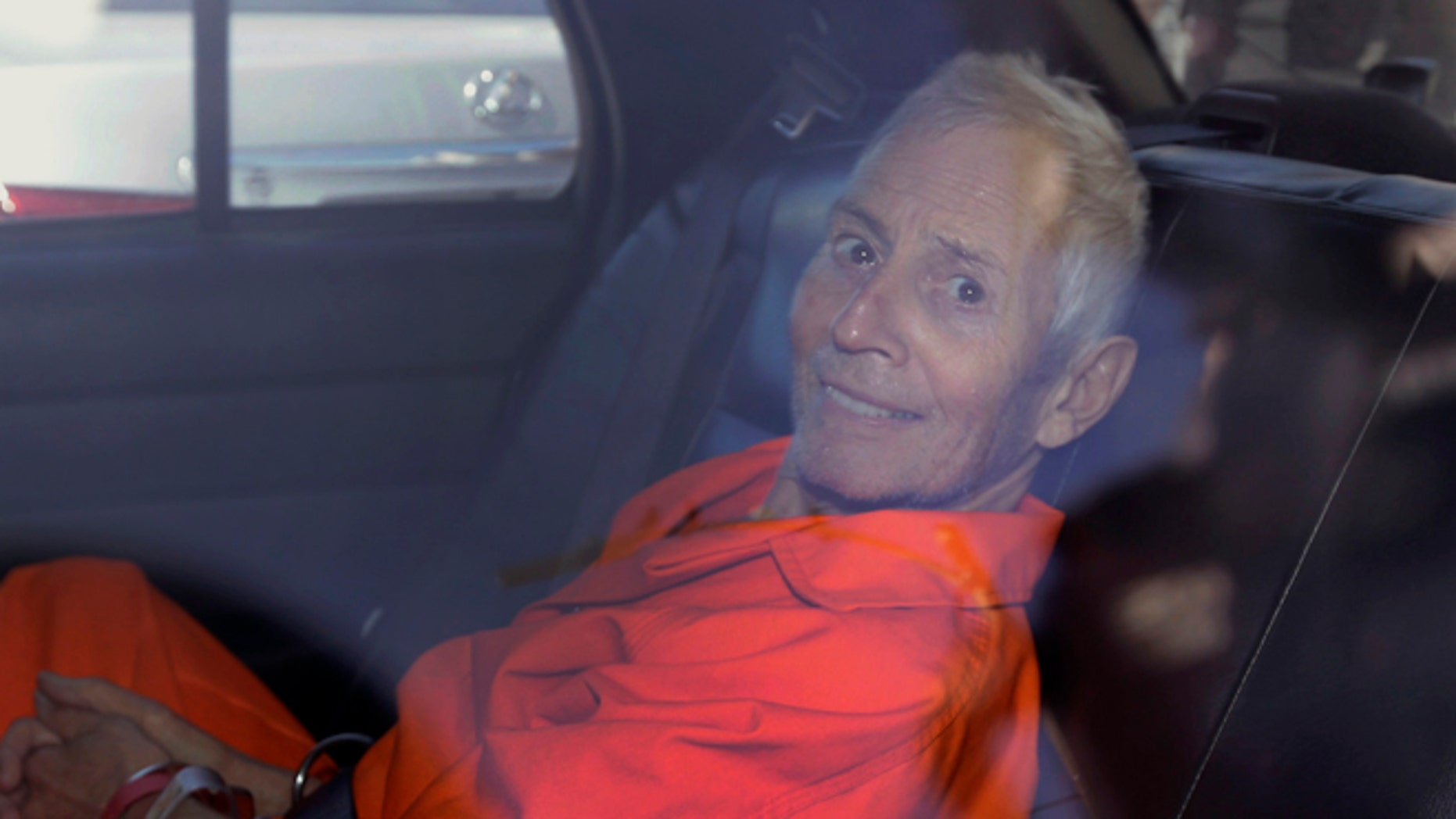 FILE - In this Tuesday, March 17, 2015, file photo, Robert Durst is transported from Orleans Parish Criminal District Court to the Orleans Parish Prison after his arraignment in New Orleans. The whispered words of Durst recorded in an unguarded moment in a bathroom could come back to haunt him - or help him - as he faces a murder charge. A possible move by prosecutors to introduce the incriminating material from a six-part documentary on his strange life and connection to three killings could back fire as interview footage did in the Michael Jackson molestation trial and the Robert Blake murder case.  (AP Photo/Gerald Herbert, File)