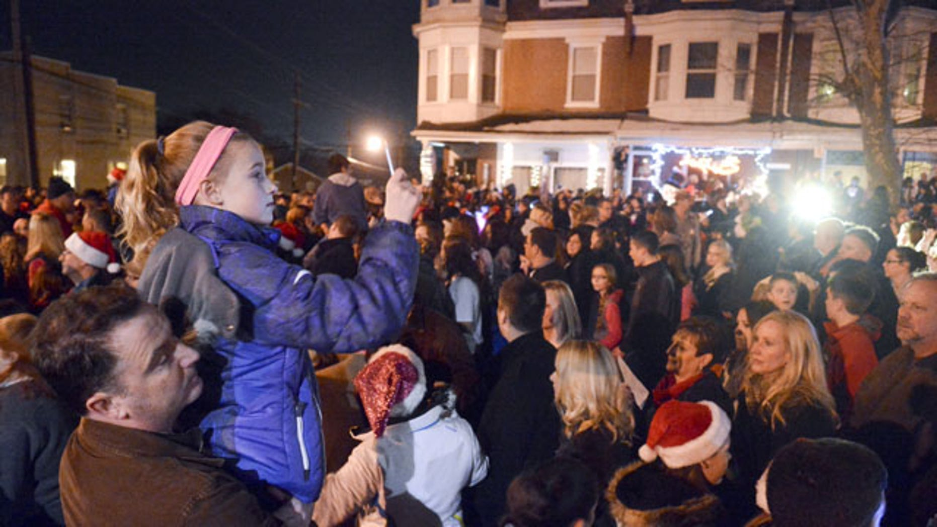 """December 21, 2013:Mike Simmons holds his daughter Gracie Simmons, 11, both of Wyomissing, while Gracie shoots video of the caroling in West Reading, Pa., where thousands of people came out to sing Christmas carols in front of the home of Delaney """"Laney"""" Brown, 8, who is terminally ill with a rare form of leukemia. (AP Photo/Reading Eagle, Ben Hasty)"""