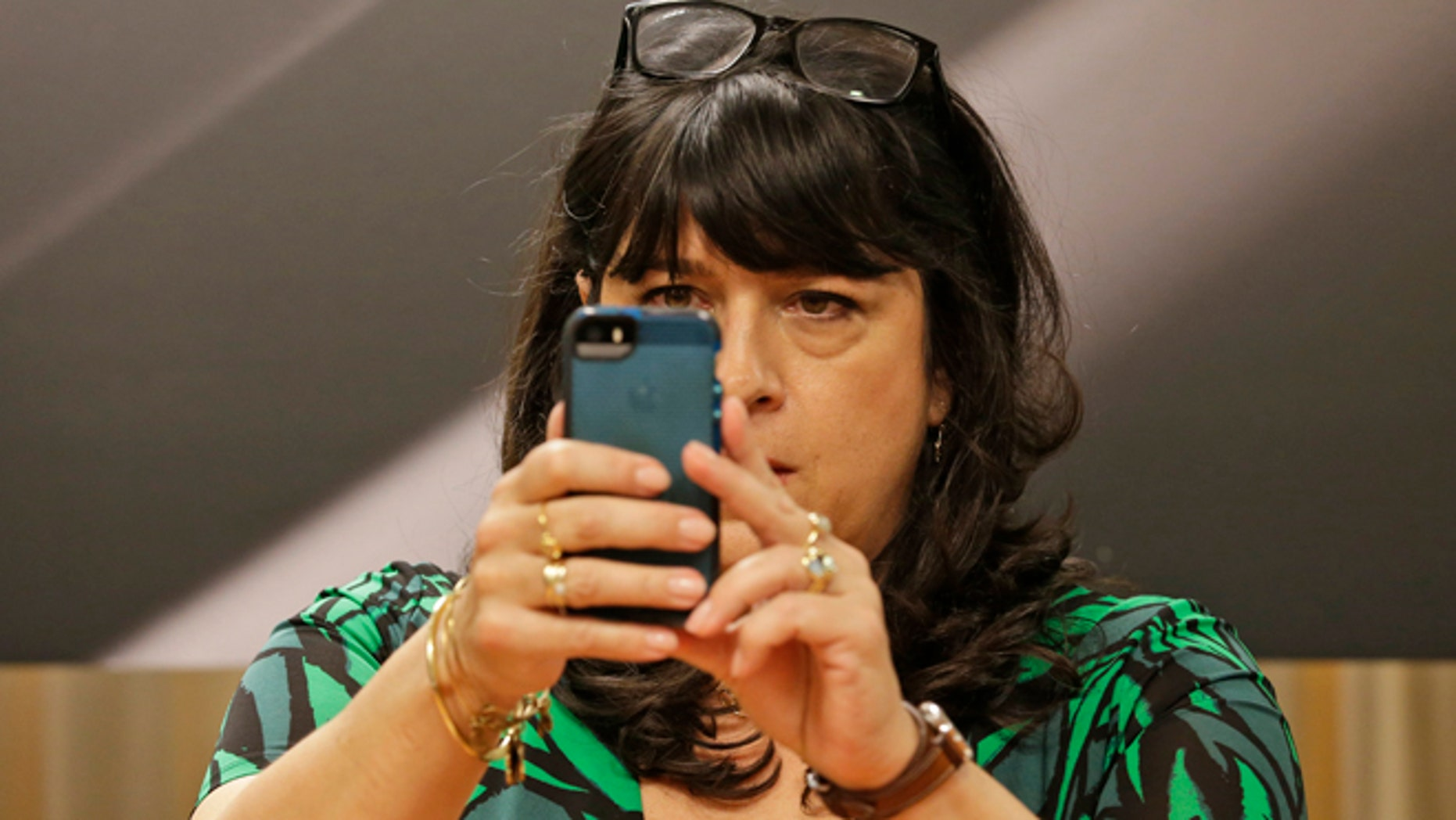 Author EL James takes a picture of photographers before signing her new book, âGrey,â at a Barnes and Noble bookstore in New York, Thursday, June 18, 2015.  (AP Photo/Mary Altaffer)