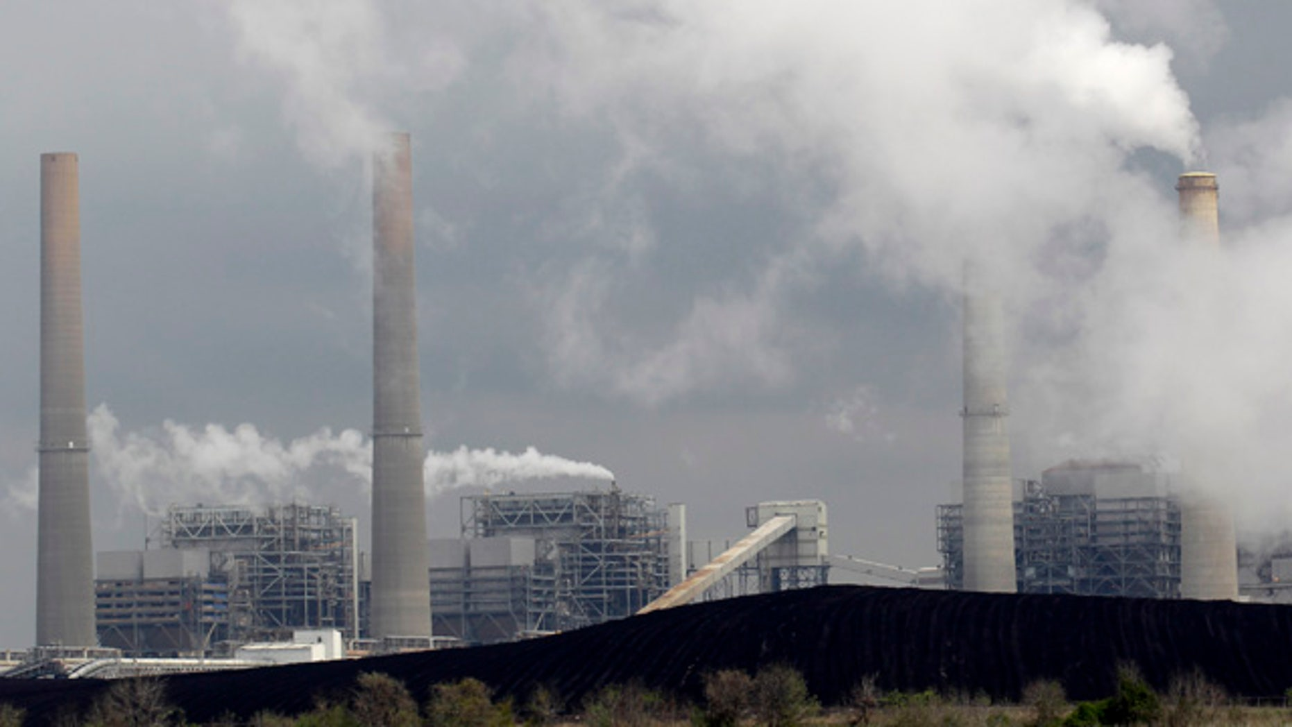 FILE - In this March 16, 2011, file photo, exhaust rises from smokestacks in front of piles of coal in Thompsons, Texas. (AP Photo/David J. Phillip, File)