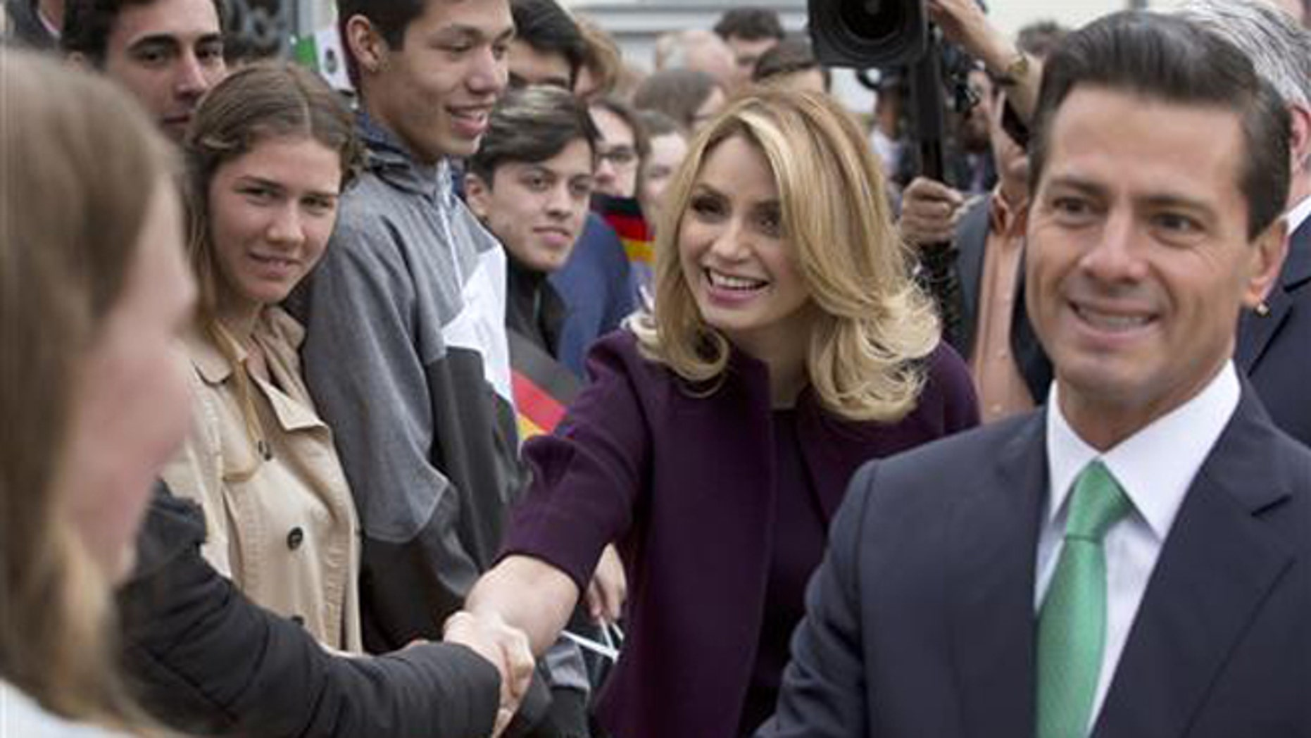 In this April 11, 2016 file photo, Mexico's President Enrique Pena Nieto, right, and his wife Angelica Rivera de Pena greet students as they arrive to meet with Germany's President Joachim Gauck at Bellevue Palace in Berlin, Germany. Pena Nieto apologized on Monday, July 18, 2016 for a 2014 scandal involving a mansion his wife bought from a firm that won lucrative contracts with his administration. (AP Photo/Michael Sohn, File)