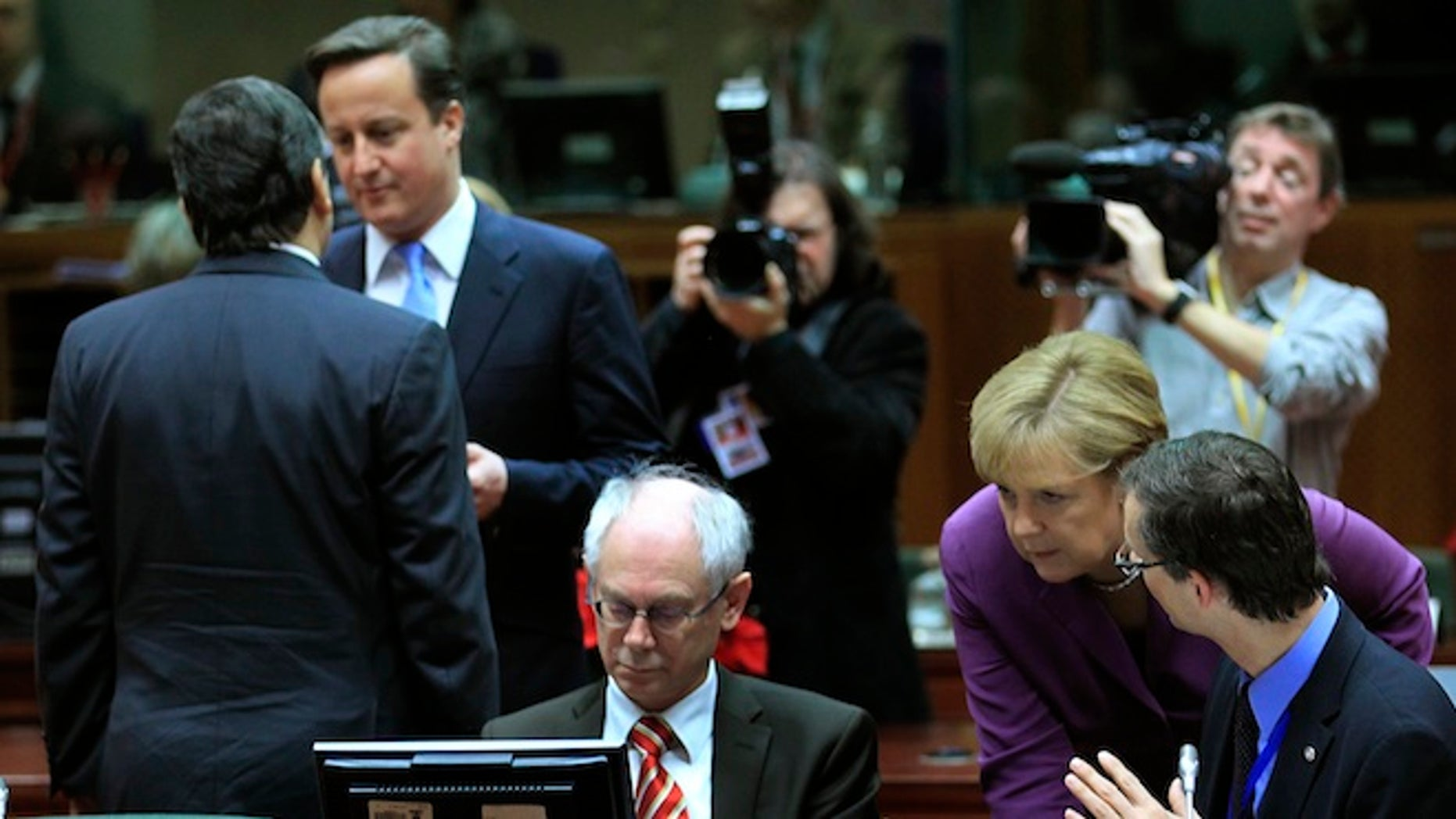 FILE: European Commission President Jose Manuel Barroso talks with Britain's Prime Minister David Cameron while Germany's Chancellor Angela Merkel (2ndR) speaks with European Council President Herman Van Rompuy (C) at a European Union summit in Brussels.