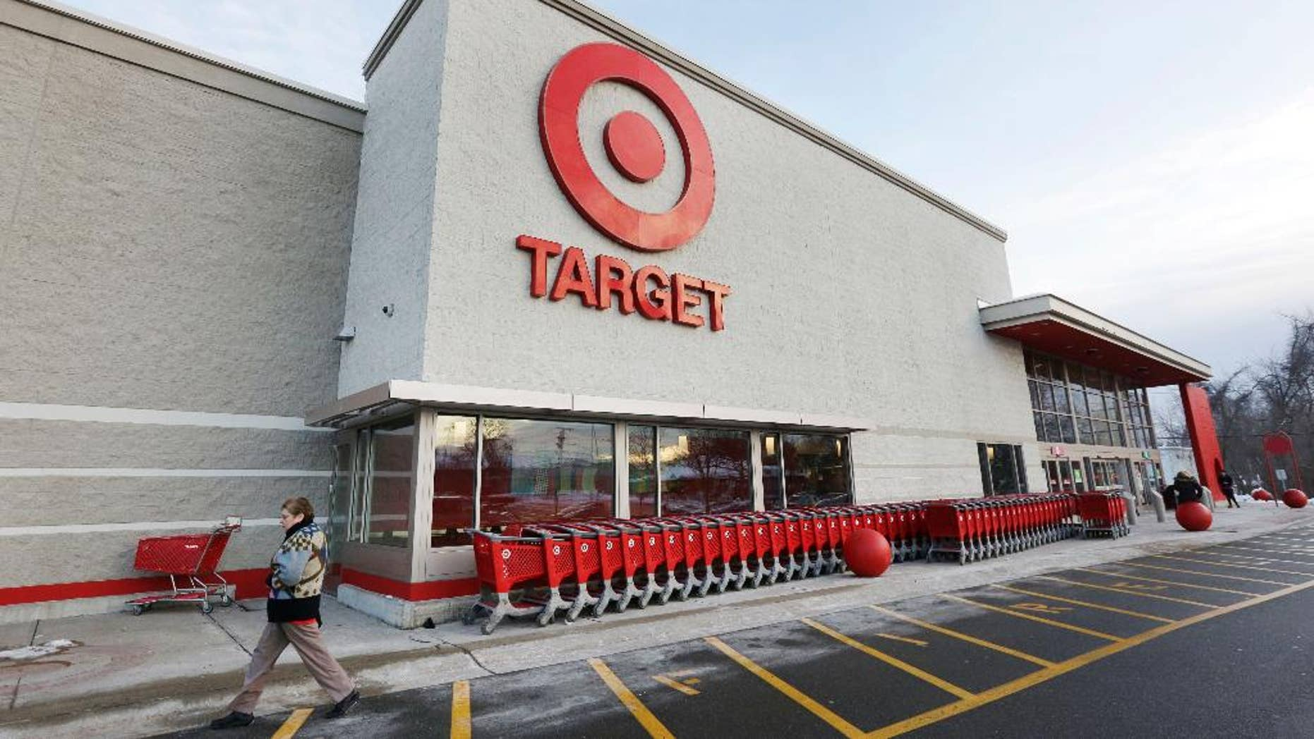 FILE - In this Dec. 19, 2013, file photo, a passer-by walks near an entrance to a Target retail store in Watertown, Mass. Target Corp. reports quarterly financial results before the market opens Wednesday, May 20, 2015. (AP Photo/Steven Senne, File)