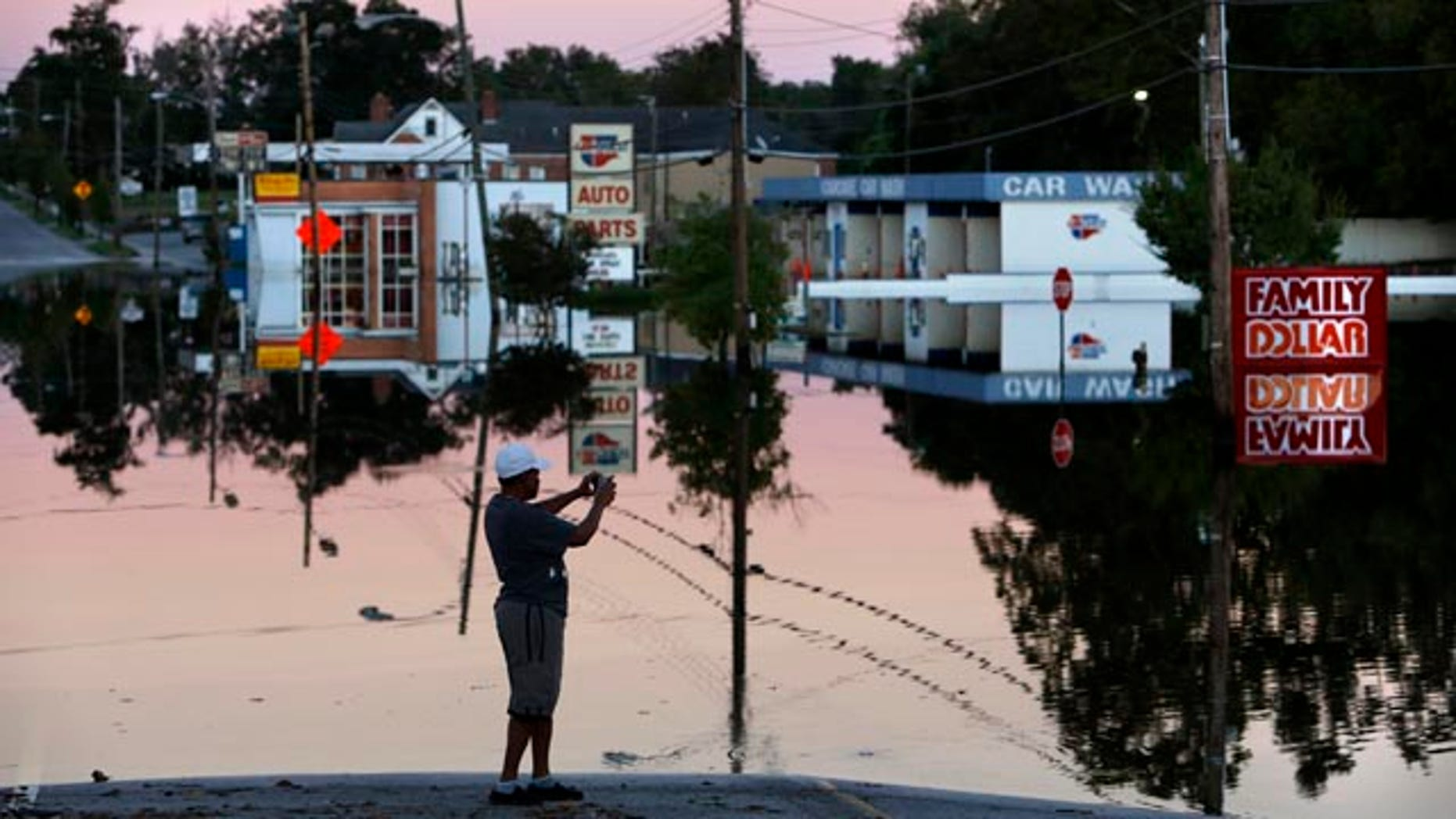 Oct. 7, 2015: Gay Miller takes photos of E. Main Street in downtown Kingstree, S.C., as the Black River floodwaters reflect in the late afternoon light. (AP Photo/Mic Smith)