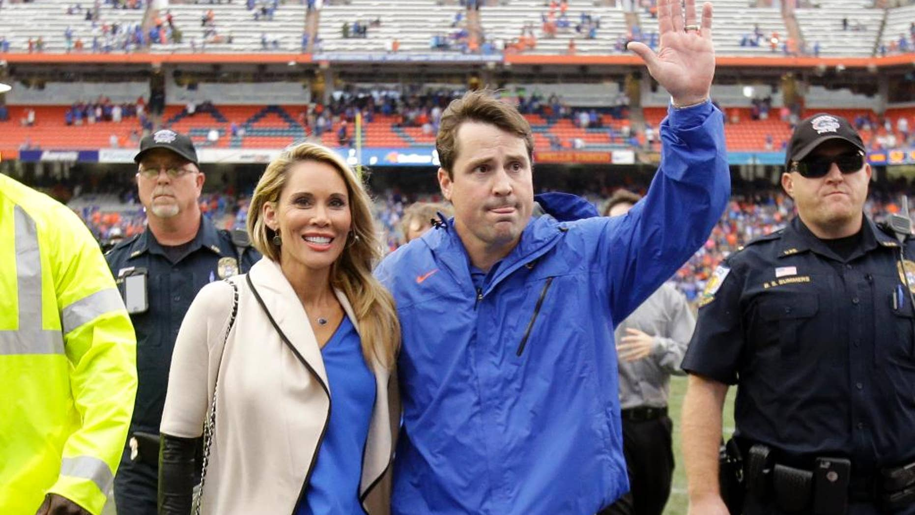 Florida head coach Will Muschamp, right, waves to cheering fans as he leaves the field with his wife Carol after an NCAA college football game against Eastern Kentucky in Gainesville, Fla., Saturday, Nov. 22, 2014.  Florida won 52-3. Muschamp was fired earlier this week, but will finish the season with the team.  (AP Photo/John Raoux)