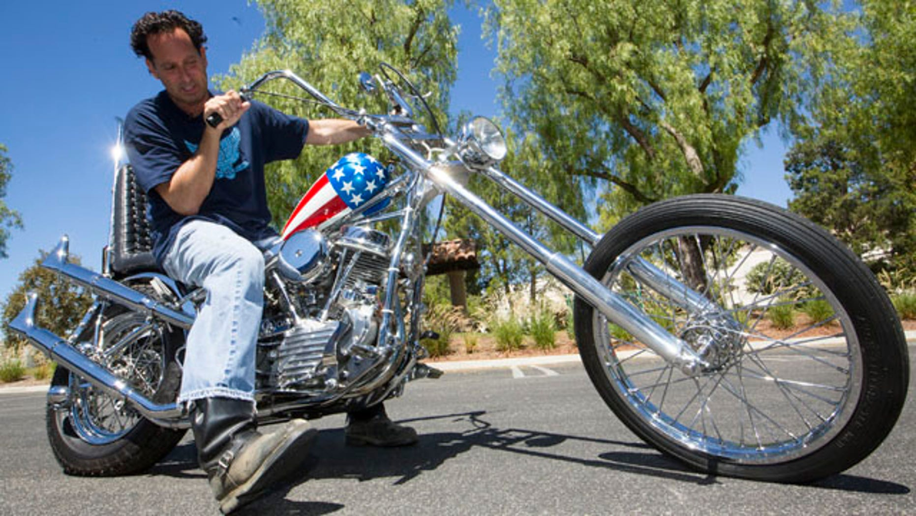 September 4, 2014: In this Thursday, Sept. 4, 2014 photo, Michael Eisenberg sits on the customized Captain America chopper Peter Fonda rode in Easy Rider at the Profiles in History auction house in Calabasas, Calif.  (AP Photo/Damian Dovarganes)