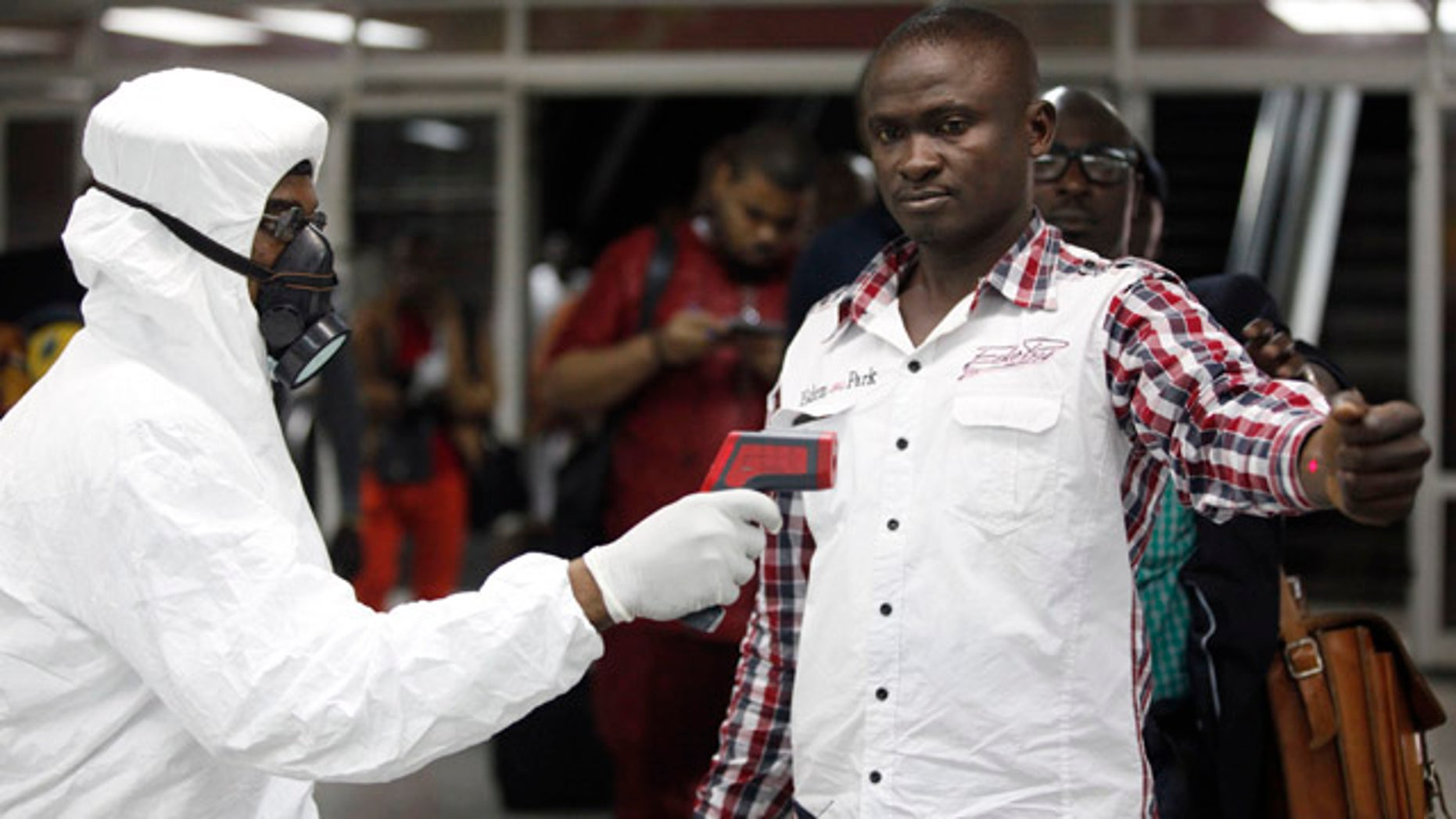 FILE - In this Aug. 6, 2014 file photo, a Nigerian port health official uses a thermometer on a worker at the arrivals hall of Murtala Muhammed International Airport in Lagos. As the Ebola outbreak in West Africa grows, airlines around the globe are closely monitoring the situation but have yet to make any drastic changes. (AP Photo/Sunday Alamba, File)