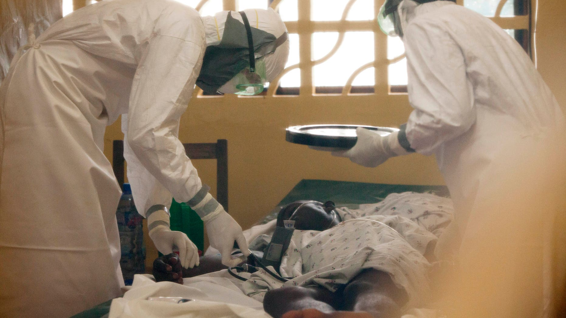 In this 2014 photo provided by the Samaritan's Purse aid organization, Dr. Kent Brantly, left, treats an Ebola patient at the Samaritan's Purse Ebola Case Management Center in Monrovia, Liberia. On Saturday, July 26, 2014, the North Carolina-based aid organization said Brantly tested positive for the disease and was being treated at a hospital in Monrovia. (AP Photo/Samaritan's Purse)