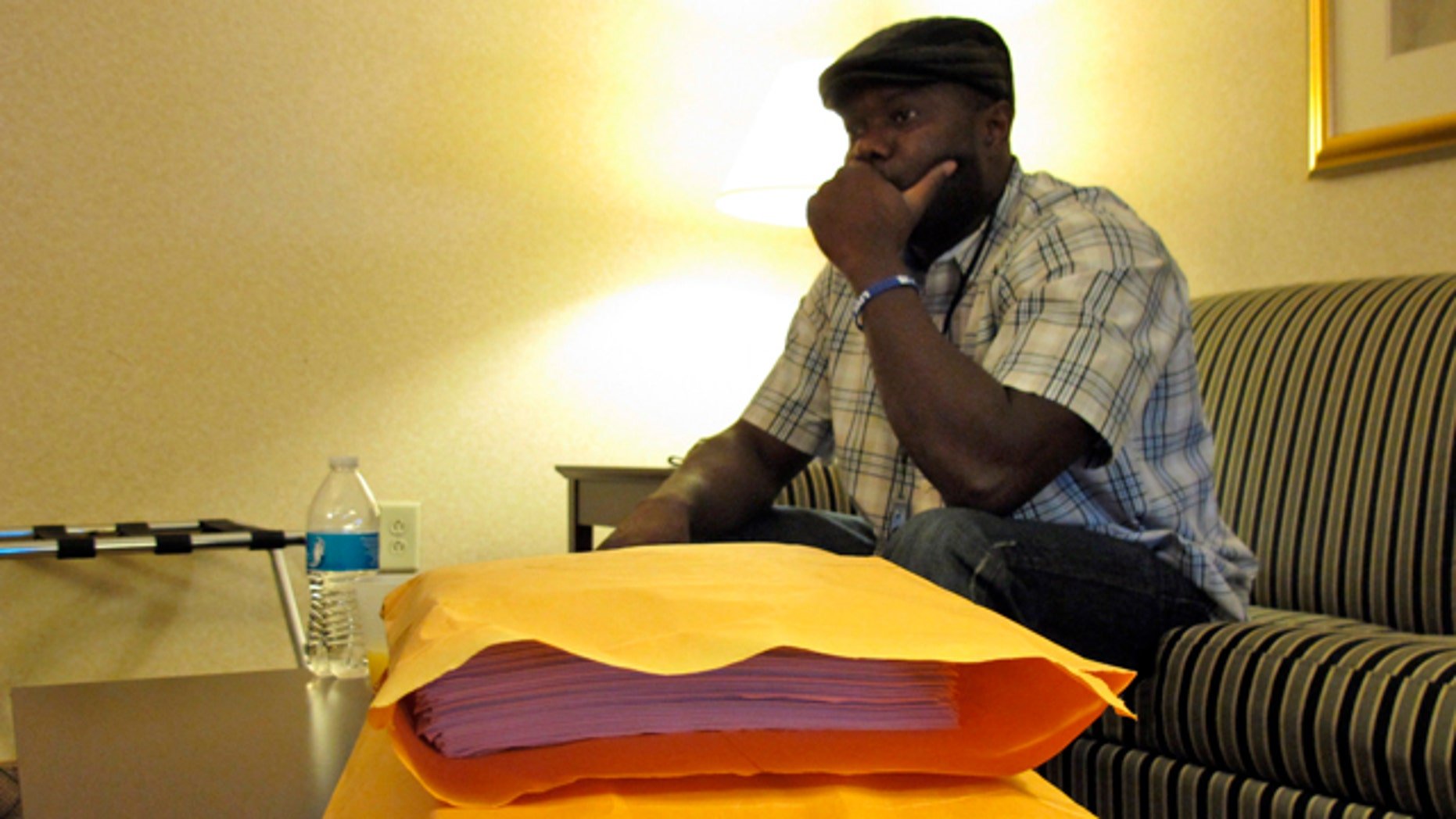 October 10, 2014: Josephus Weeks, nephew of Ebola patient Thomas Eric Duncan who died earlier this week in Dallas, sits behind a stack of medical documents in a hotel room in Kannapolis, N.C. (AP Photo/Allen G. Breed)