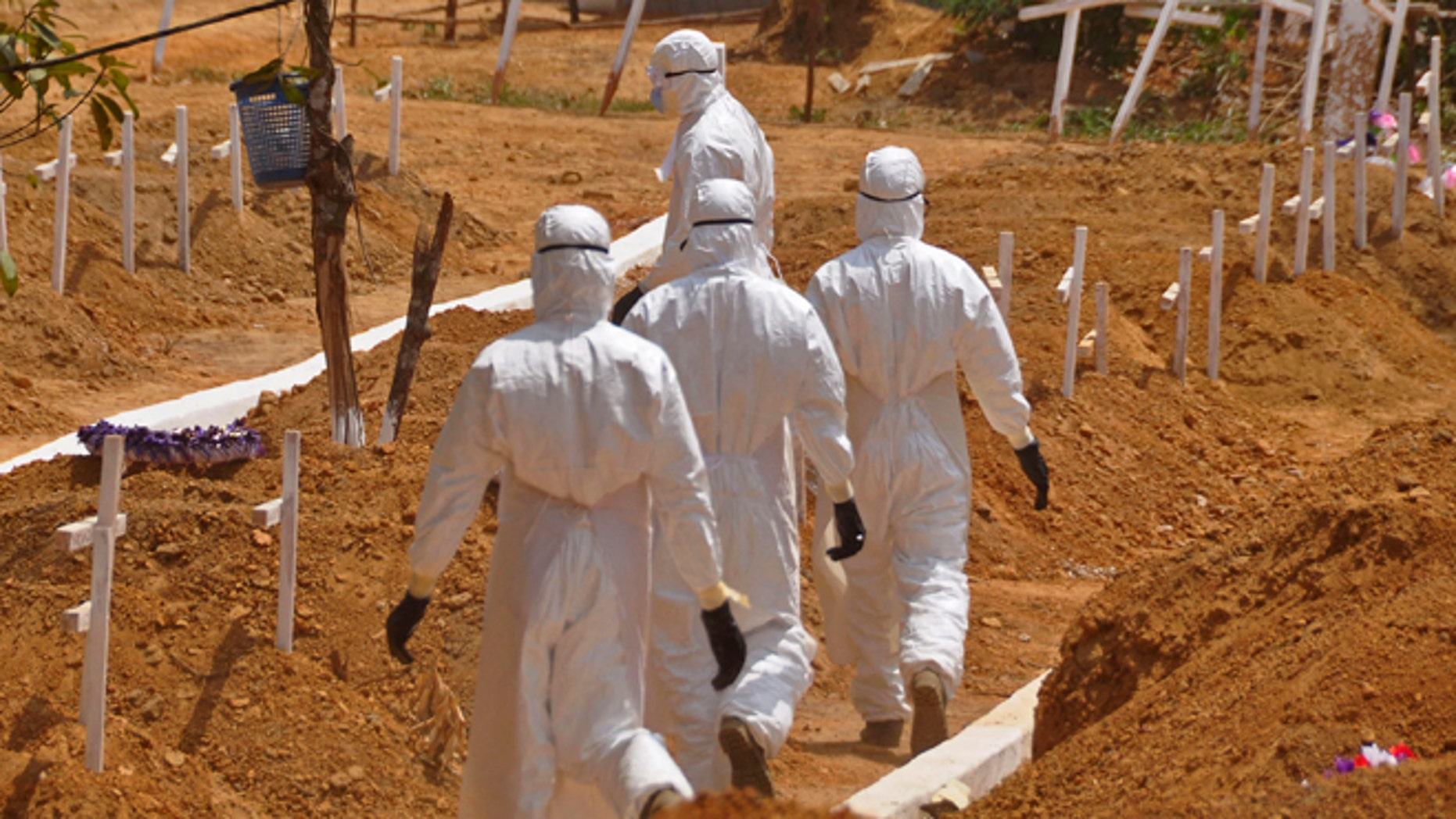 FILE- In this file photo dated Wednesday, March 11, 2015, health workers walk inside a new graveyard for Ebola victims, on the outskirts of Monrovia, Liberia. Despite the drop in reported Ebola cases, Dr. Bruce Aylward, leading WHOs Ebola response, declared Friday April 10, 2015, that its too early for World Health Organization to downgrade the global emergency status of the biggest-ever Ebola outbreak in Africa. (AP Photo/Abbas Dulleh, FILE)