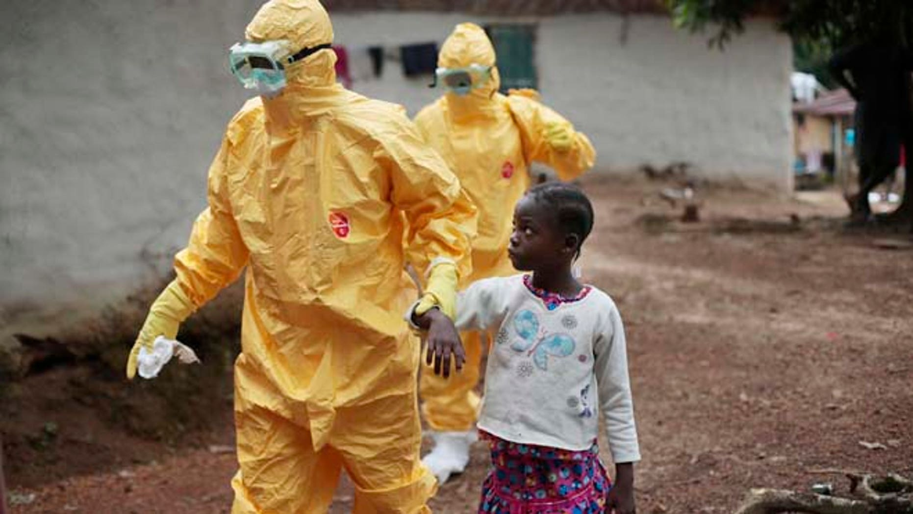 FILE 2014: Nine-year-old Nowa Paye is taken to an ambulance after showing signs of the Ebola virus disease in the village of Freeman Reserve, which is north of Monrovia, Liberia.