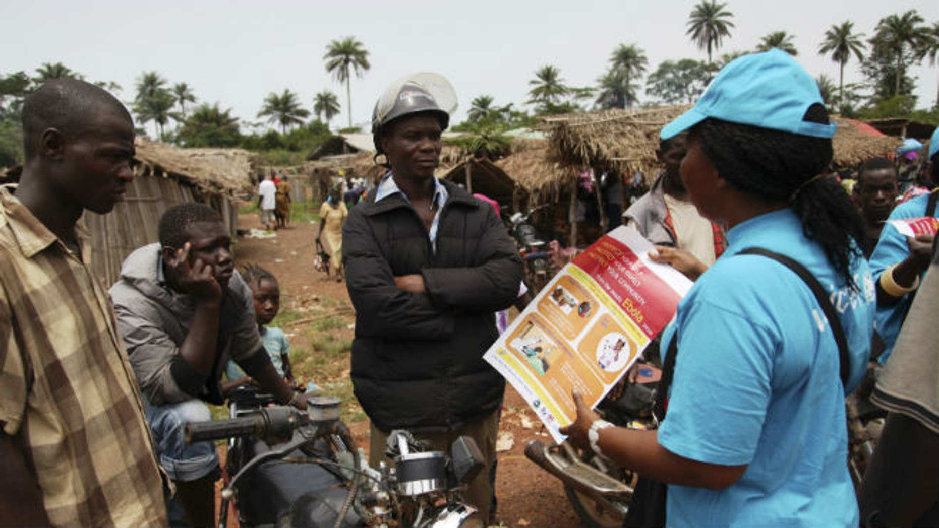 A UNICEF worker speaks with drivers of motorcycle taxis about the symptoms of Ebola virus disease (EVD) and best practices to help prevent its spread, in the city of Voinjama, in Lofa County, Liberia in this April 2014 UNICEF handout photo. (REUTERS/Ahmed Jallanzo/UNICEF)