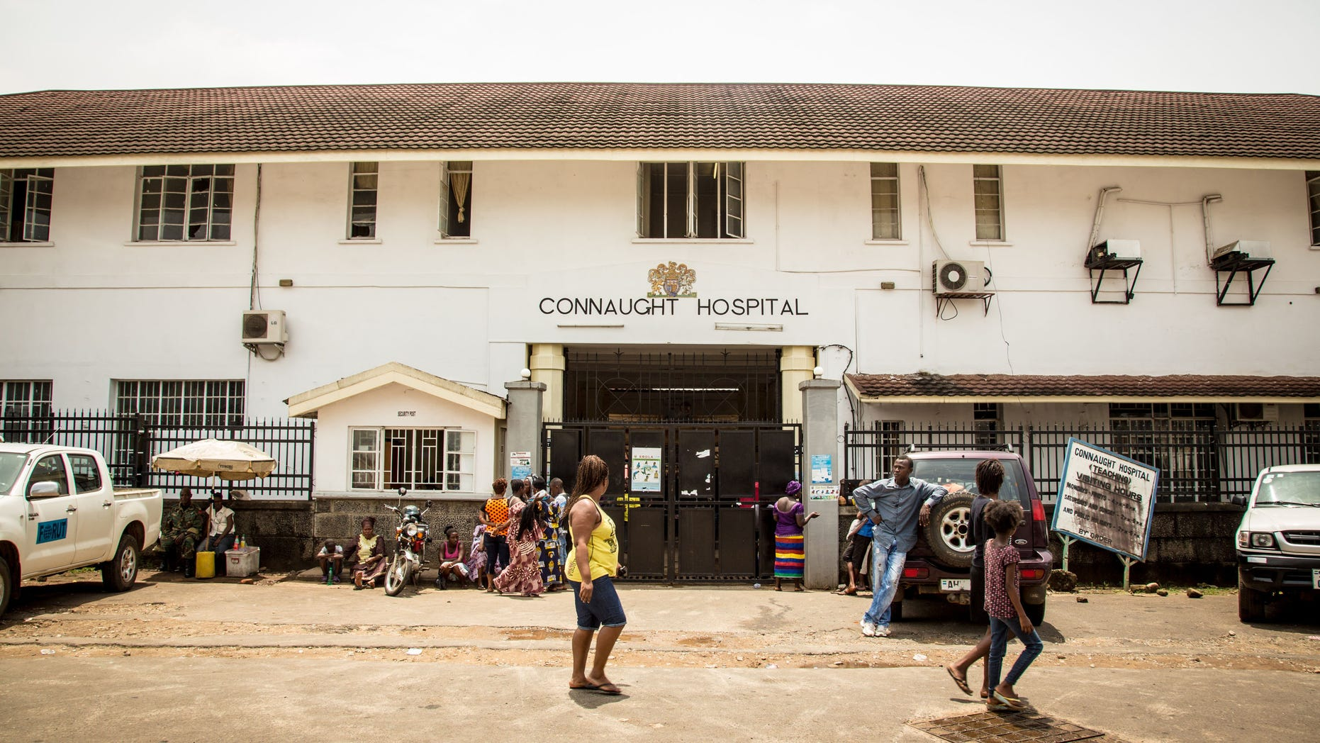 In this photo taken on Sunday,  Sept. 14, 2014,  people walk past the Connaught Hospital that is used for treating people suffering from the Ebola virus in Freetown, Sierra Leone.  (AP Photo/ Michael Duff)