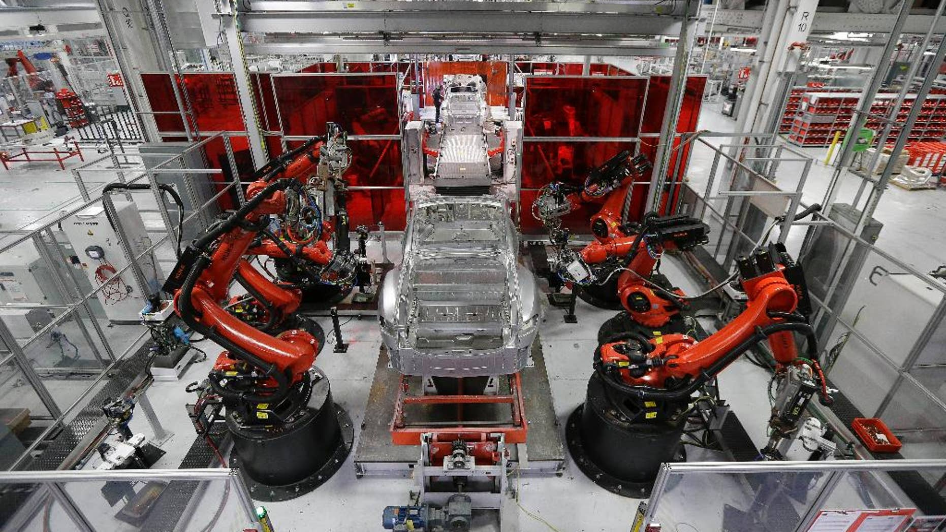 In this May 14, 2015 photo, Kuka robots work on Tesla Model S cars in the Tesla factory in Fremont, Calif. The Institute for Supply Management, a trade group of purchasing managers, issues its index of manufacturing activity for May on Monday, June 1, 2015. (AP Photo/Jeff Chiu)