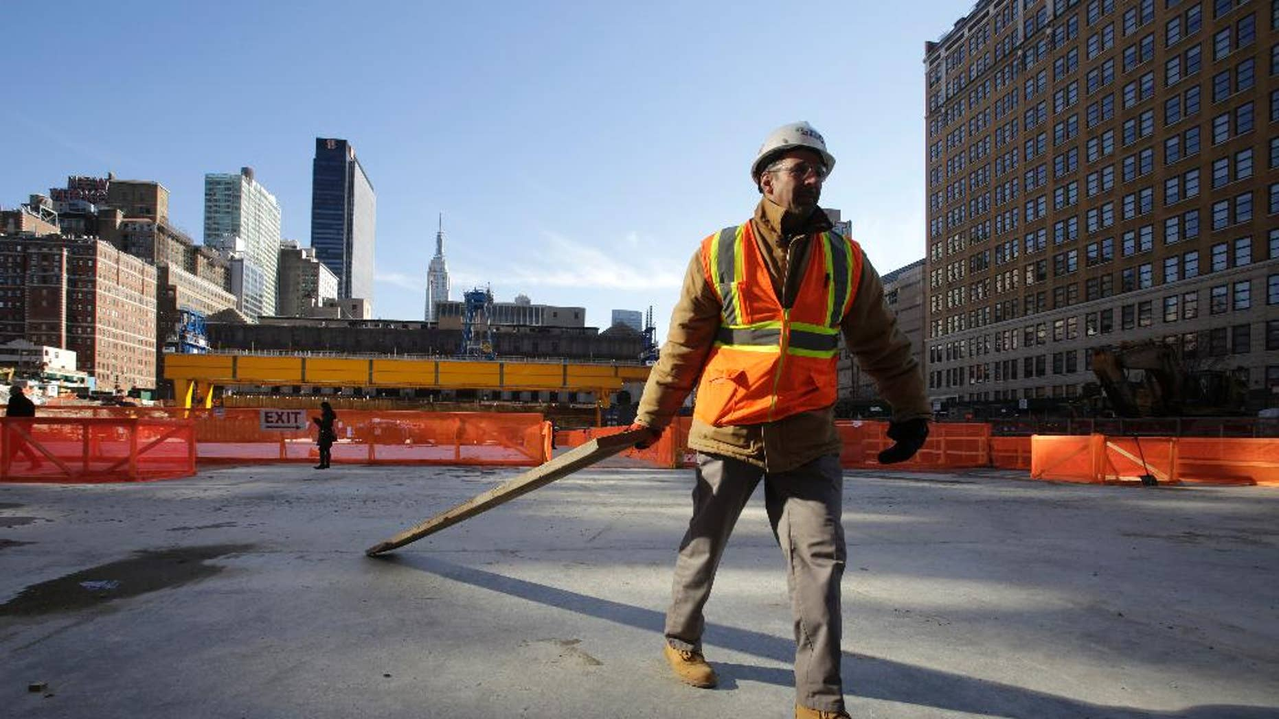 FILE - In this Nov. 18, 2014 file photo, a construction worker clears wood from a platform that spans the Penn Station railroad tracks in midtown Manhattan, in New York. The Institute for Supply Management, a trade group of purchasing managers, issues its index of non-manufacturing activity for December on Tuesday, Jan. 6, 2015. (AP Photo/Mark Lennihan, File)