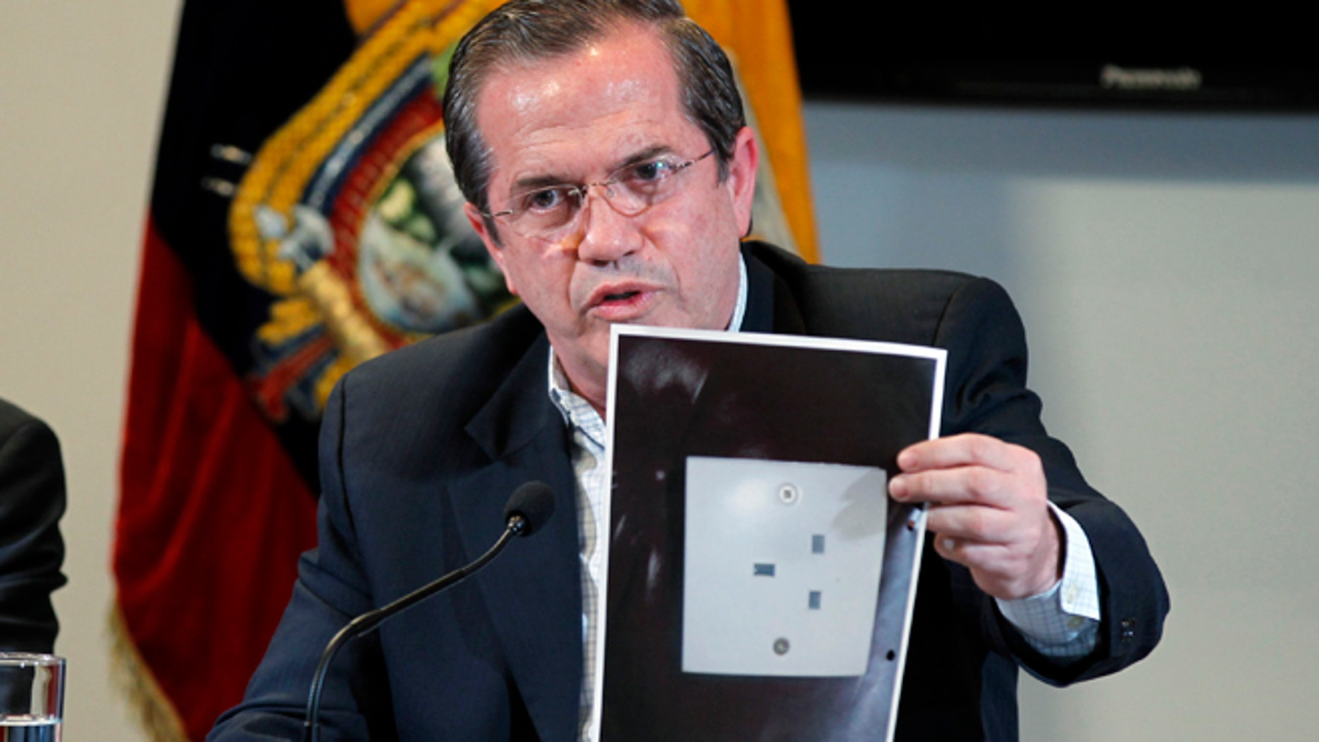 "Ecuador's Foreign Minister Ricardo Patino holds up a photograph of what he says is the electric socket at his country's embassy in London where a hidden microphone was found, during a press conference in London in Quito, Ecuador, Wednesday, July 3, 2013. Patino said that two weeks ago a hidden microphone was found where Wikileaks founder and publisher Julian Assange is holed up. ""We want to find out with precision what the origin of the apparatus is.""  (AP Photo/Dolores Ochoa)"