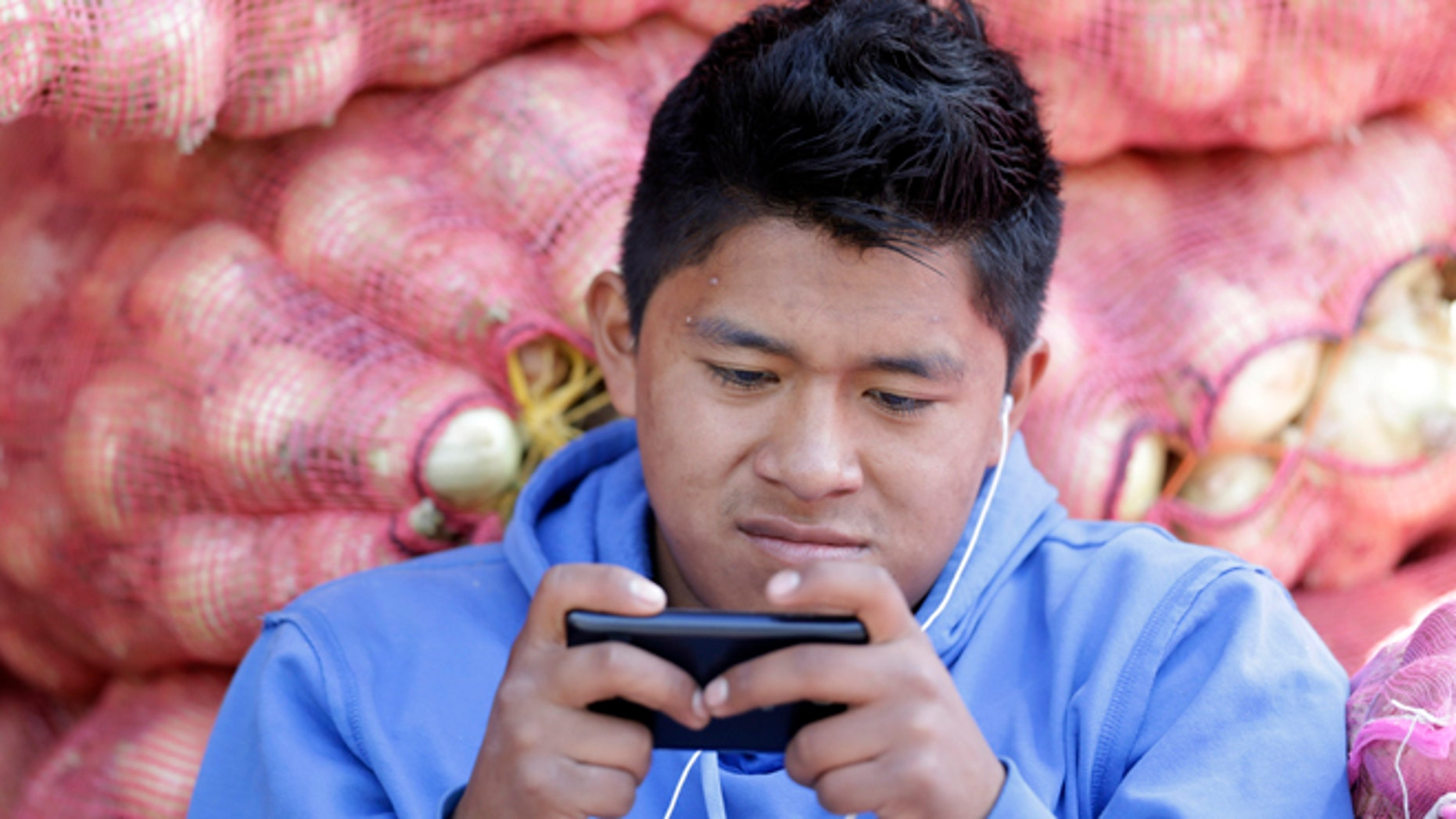 In this Aug. 24, 2014, photo, a young man texts a message on his mobile phone while working at the Mayorista Market in Quito, Ecuador. Ecuador's Central Bank is getting ready to use electronic currency in which consumers will initially be able to use it to make and receive payments using their cellphones. Ecuador is heralding its plans to create the worlds first government-issued digital currency, which some analysts believe could ultimately replace the countrys existing currency, the U.S. dollar, which the government cannot control.  (AP Photo/Dolores Ochoa)