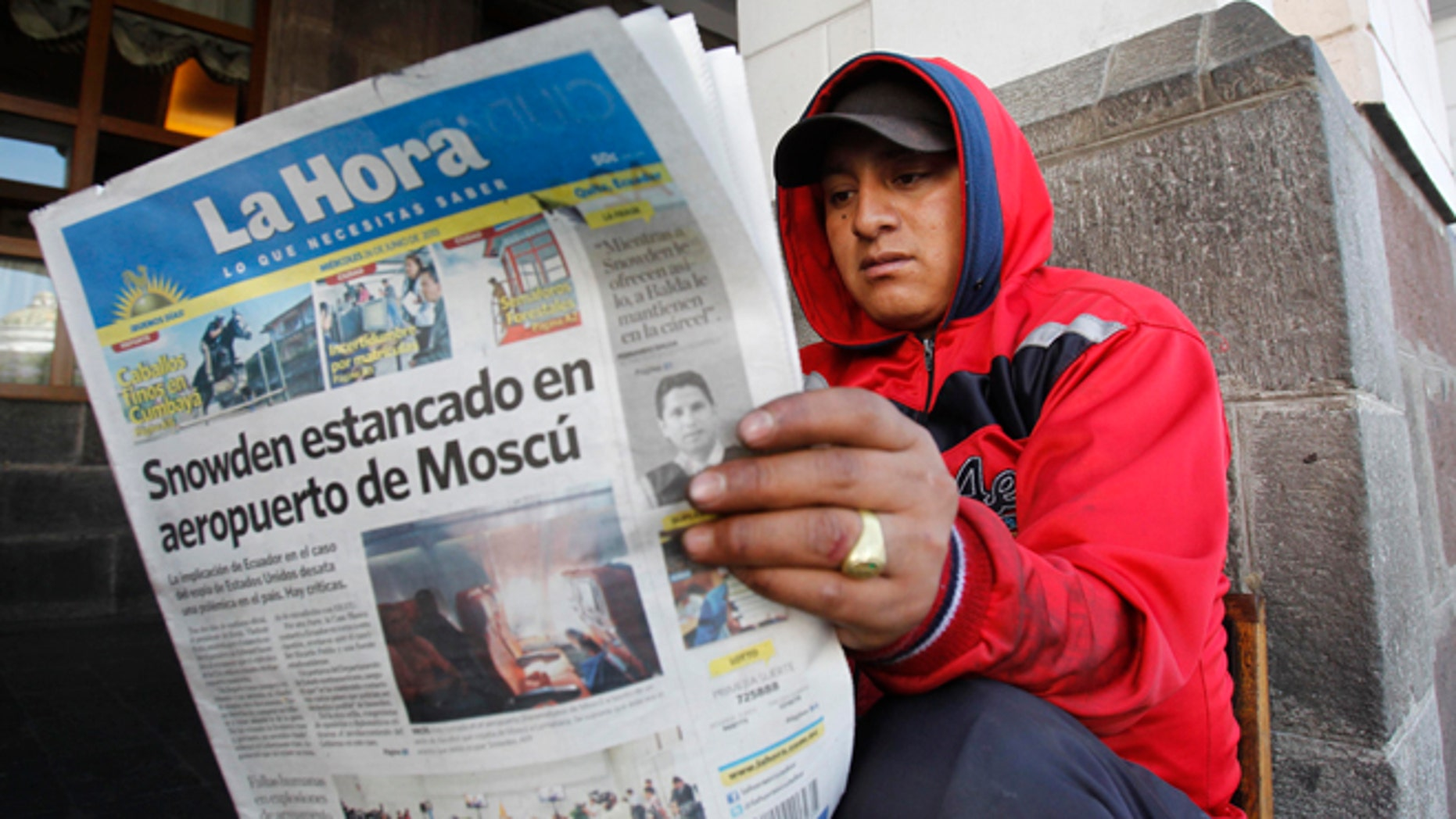 """A man reads a newspaper with the headline in Spanish """"Snowden stuck at Moscow airport"""" in Quito, Ecuador, June 26, 2013."""