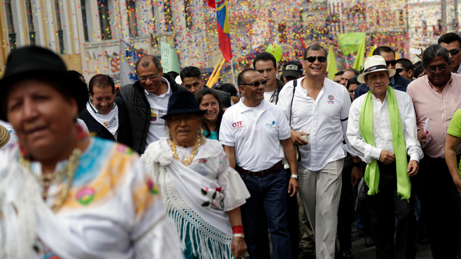 FILE - In this Friday, May 1, 2015, file photo, Ecuador's President Rafael Correa, third from the right, marches in the May Day parade in Quito, Ecuador. Ecuadors leader halted his motorcade when a 16-year-old appeared to make an obscene gesture at him, Correa got out and confronted the teenager. Officials say the boy was detained and later sentenced to 20 hours of community service for making offensive gestures at the president on May 1. (AP Photo/Dolores Ochoa, File)