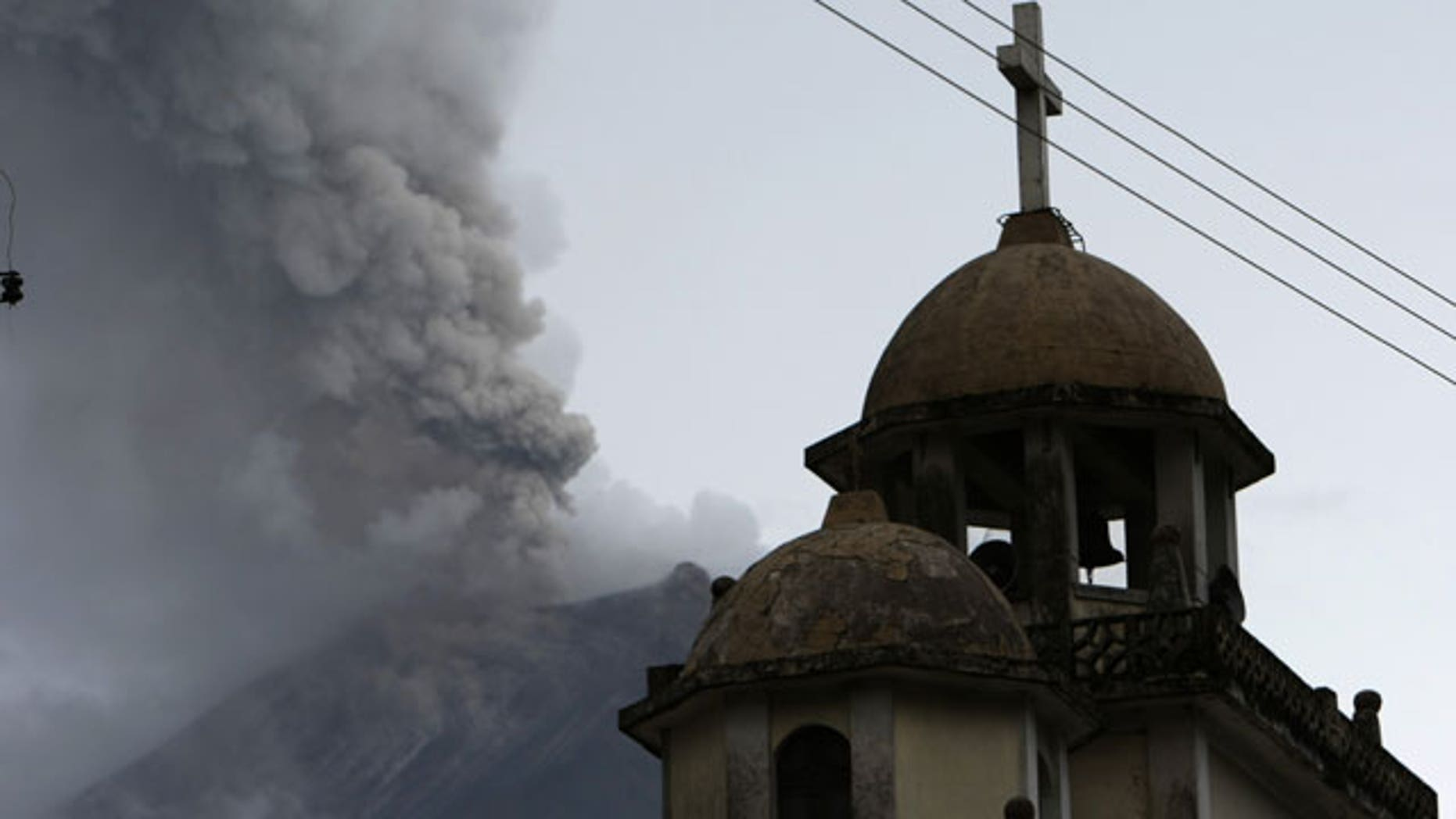 A view of Cotalo's church, backdropped by the Tungurahua volcano spewing ashes in Cotalo, central Ecuador, Friday, May 28, 2010. The Tungurahua has been constantly erupting since 1999.