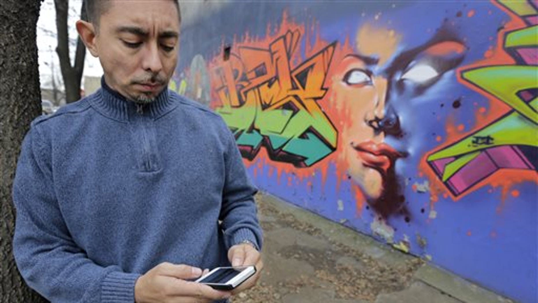 "In this Dec. 6, 2013 photo, Eddie Bocanegra, co-executive director of the YMCA of Metropolitan Chicago's Youth Safety and Violence Prevention program, stands with his phone outside the organization's center in the Pilson neighborhood of Chicago. With the advent of social media usage by gangs, he says, ""In the past you would have gangs approach you and say, 'Listen we're from the 'hood. Maybe you should get involved.' Now the kids are going to the gangs saying, 'I saw this. How can I be a part of it?'"" (AP Photo/M. Spencer Green)"